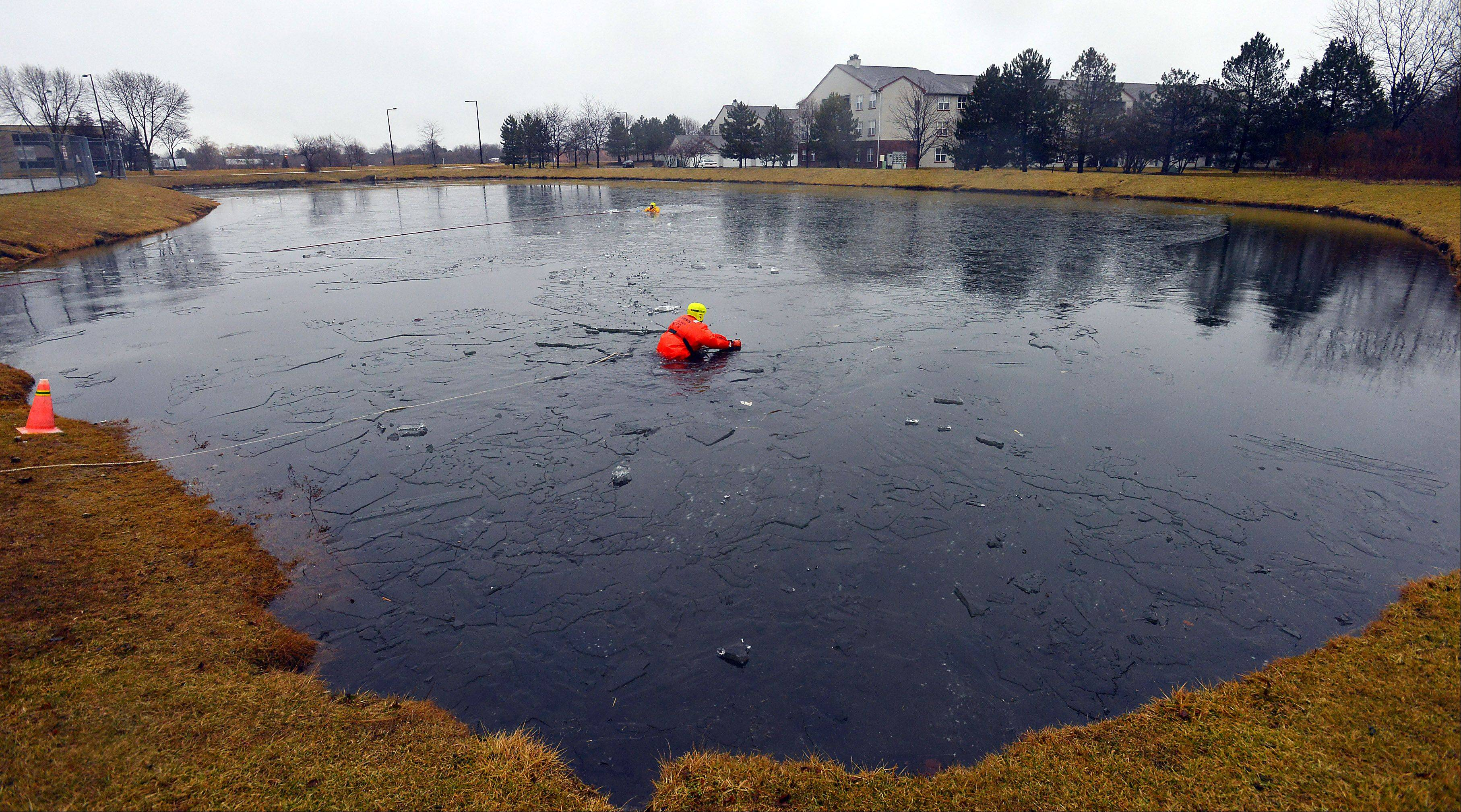 Firefighters from different departments from across the Northwest suburbs braved the elements to practice their ice rescue drills at the retention pond at the Combined Area Fire Training Facility in Buffalo Grove on Wednesday.