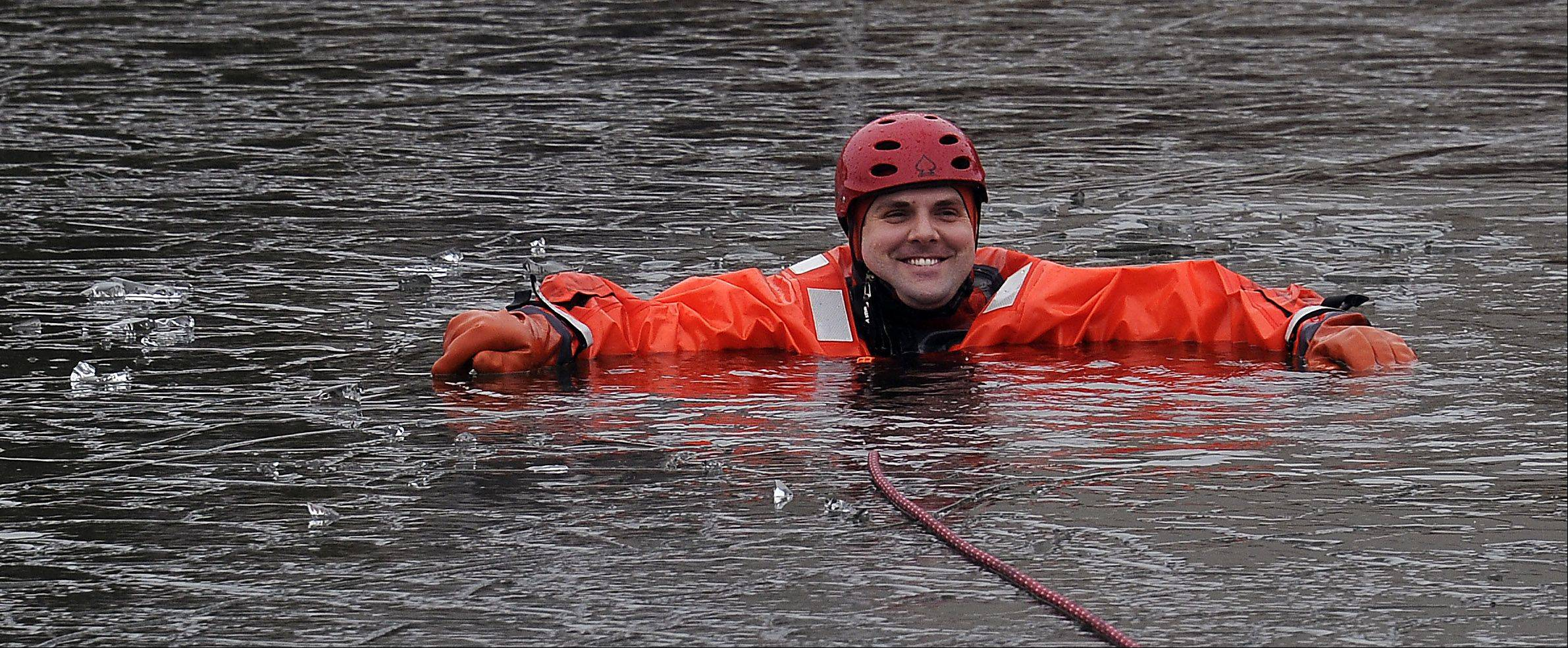Firefighter/paramedic rescue victim Nick Otto from the Buffalo Grove Fire Department is all smiles as he waits in his dry suit to be rescued by fellow firefighters. They were practicing their drills at the retention pond located next to the Combined Area Fire Training Facility in Buffalo Grove on Wednesday.