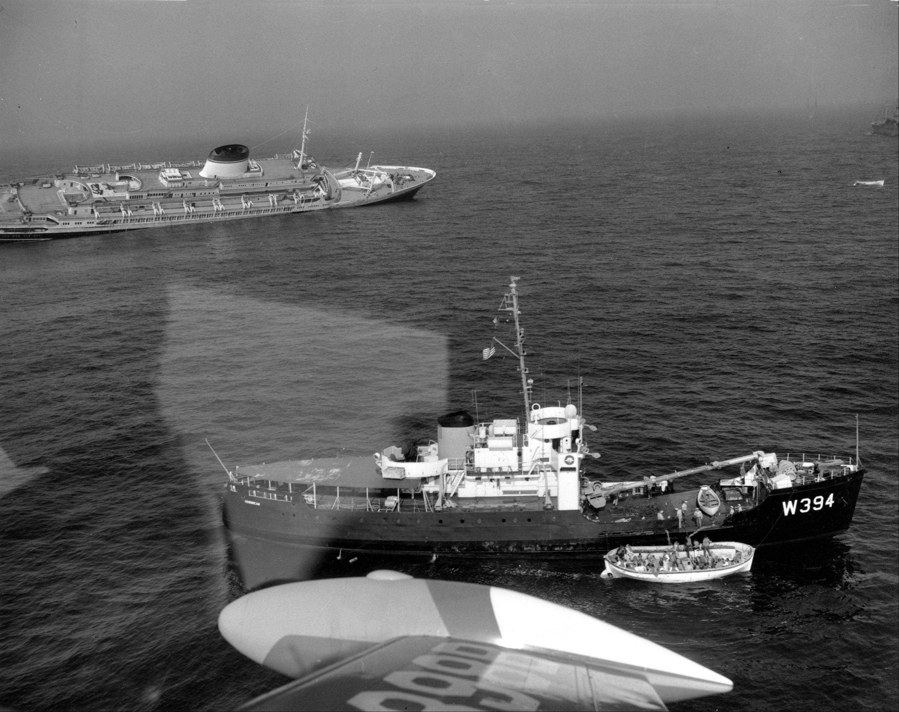 A lifeboat of passengers is alongside a rescue vessel as the liner Andrea Doria sinks in the background on July 26, 1956. The Italian liner collided with the Swedish liner Stockholm off Nantucket Island, Ma., last night. The reflection in center is halation from the plane window through which this photograph was taken.