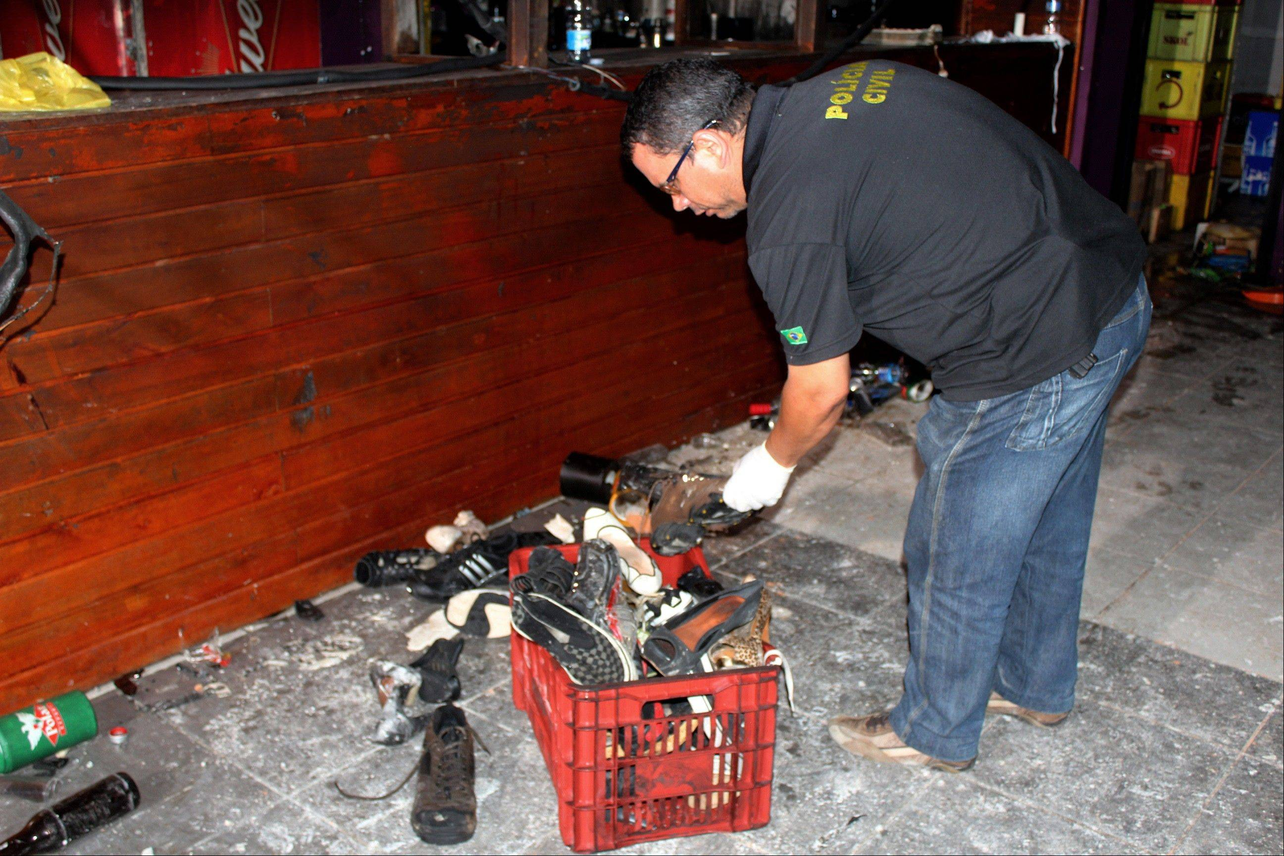 A police officer inspects victims' belongings after a fire at the Kiss nightclub in Santa Maria City, Rio Grande do Sul state, Brazil, Tuesday, Jan. 29, 2012. The blaze began at around 2:30 a.m. local time on Sunday, during a performance by Gurizada Fandangueira, a country music band that had made the use of pyrotechnics a trademark of their shows.