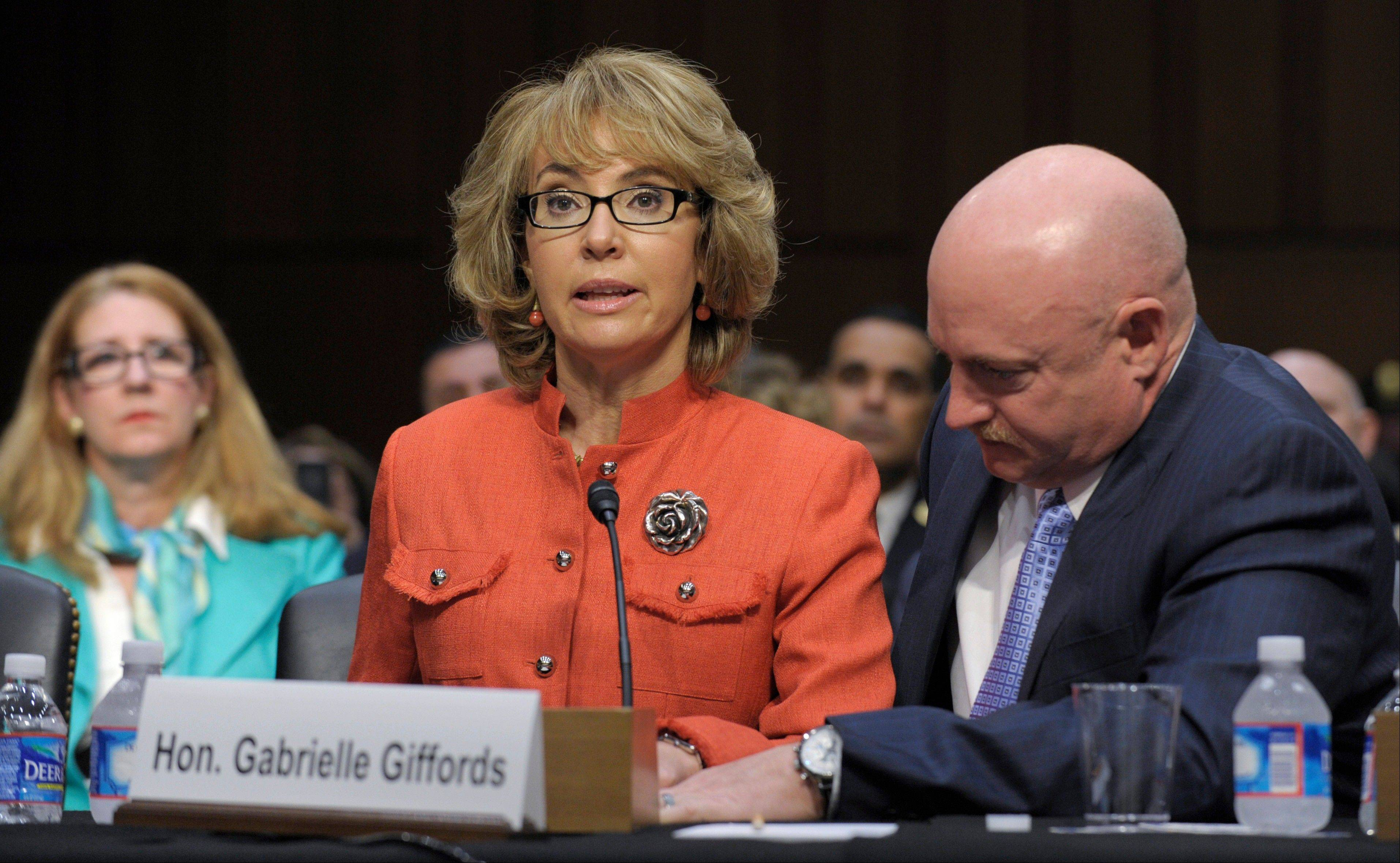 Former Arizona Rep. Gabrielle Giffords, who was seriously injured in the mass shooting that killed six people in Tucson, Ariz., two years ago, sits with her husband, Mark Kelly, Wednesday and speaks before the Senate Judiciary Committee hearing on gun violence.