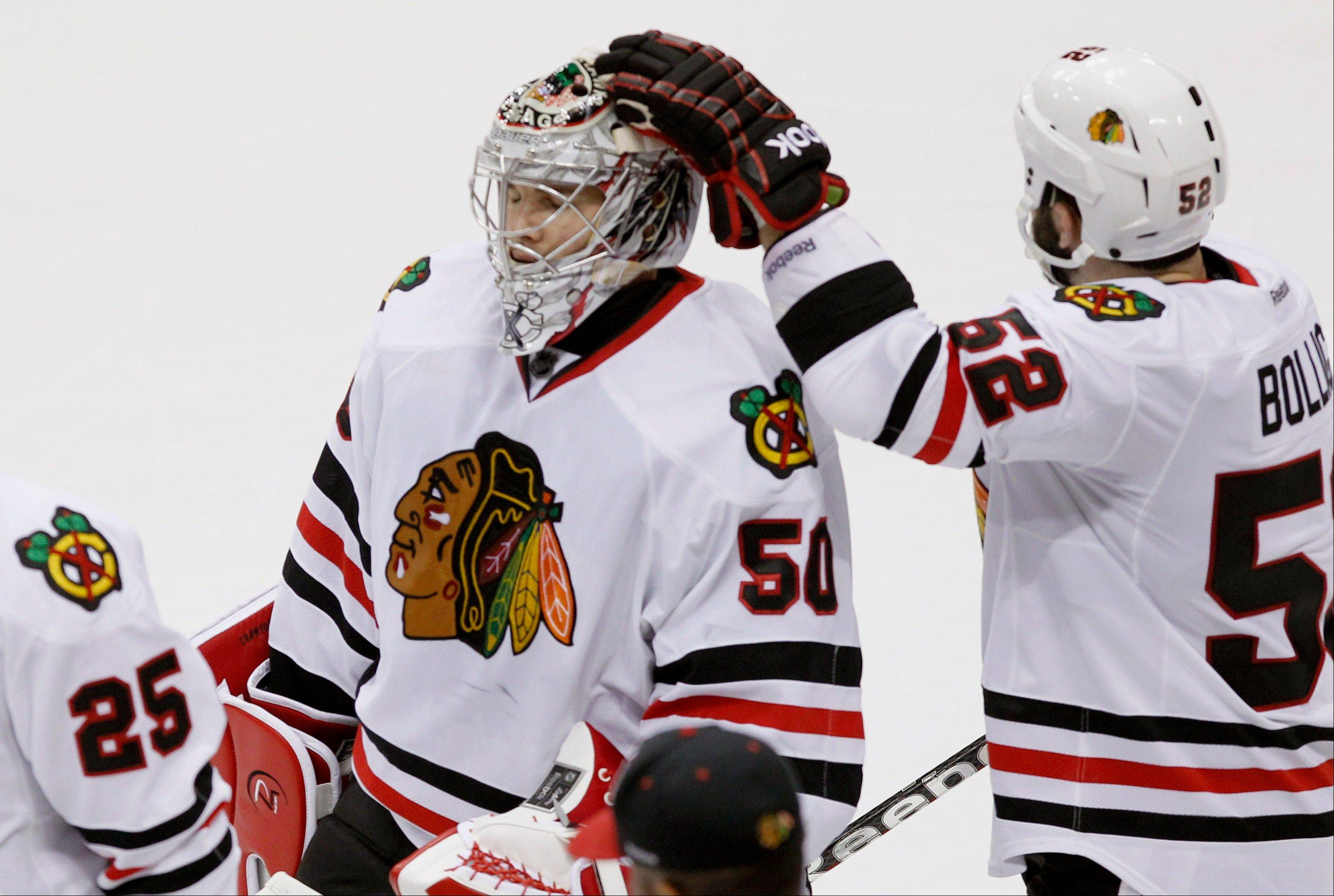Blackhawks goalie Corey Crawford gets a pat on the helmet from Brandon Bollig after the Minnesota Wild won 3-2 in a shootout Wednesday night.