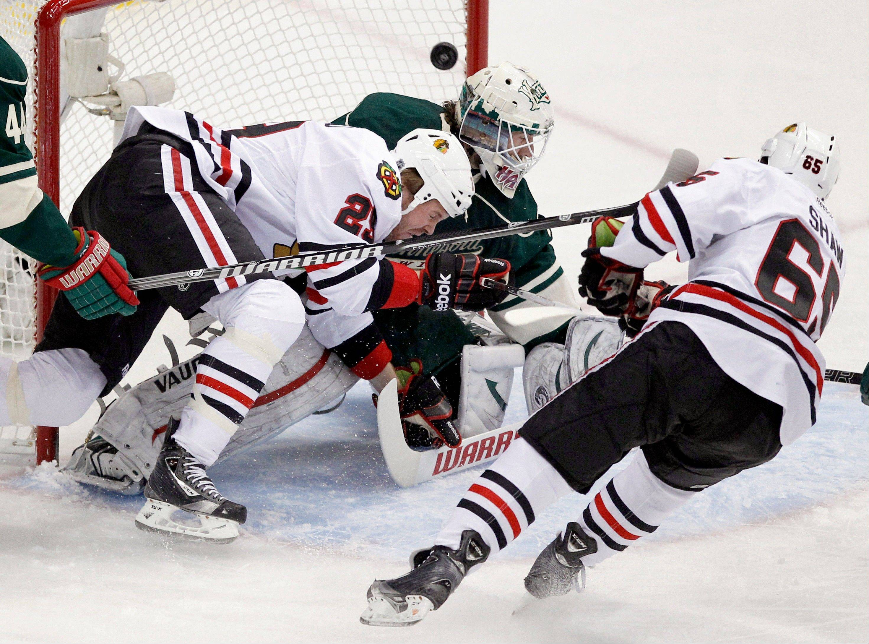 Chicago Blackhawks center Andrew Shaw (65) scores on Minnesota Wild goalie Josh Harding as Blackhawks' Bryan Bickell (29) pressures the goalie during the Chicago-Minnesota game Wednesday in St. Paul. The Wild handed the Blackhawks their first loss of the season.