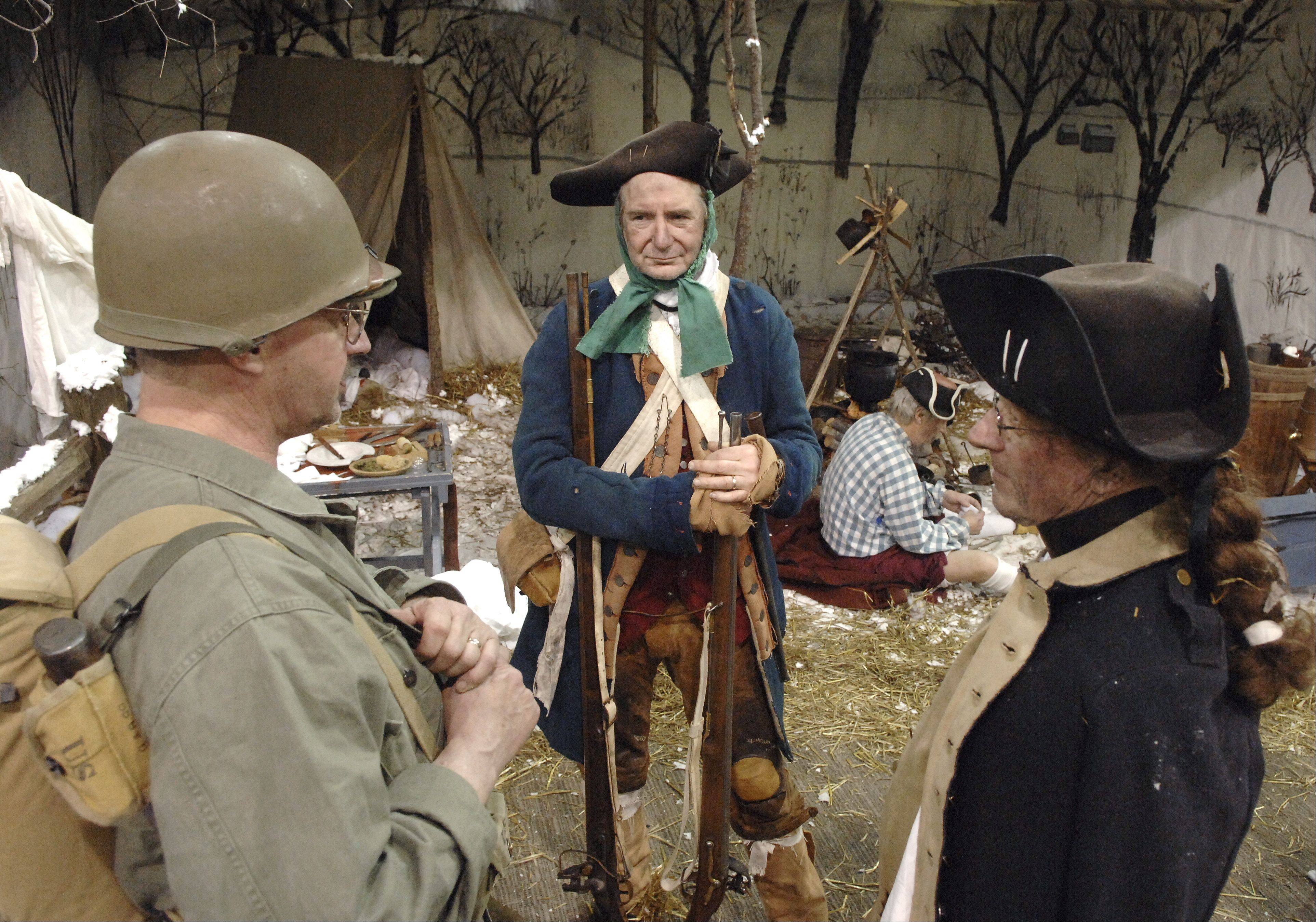 From left, re-enactors John Sauter of Paddock Lake, Wi., Al Potyen of Glen Ellyn and Bill Hess of Janesville, Wi., chat at a Valley Forge scene at last year's Military History Fest at Pheasant Run, St. Charles.