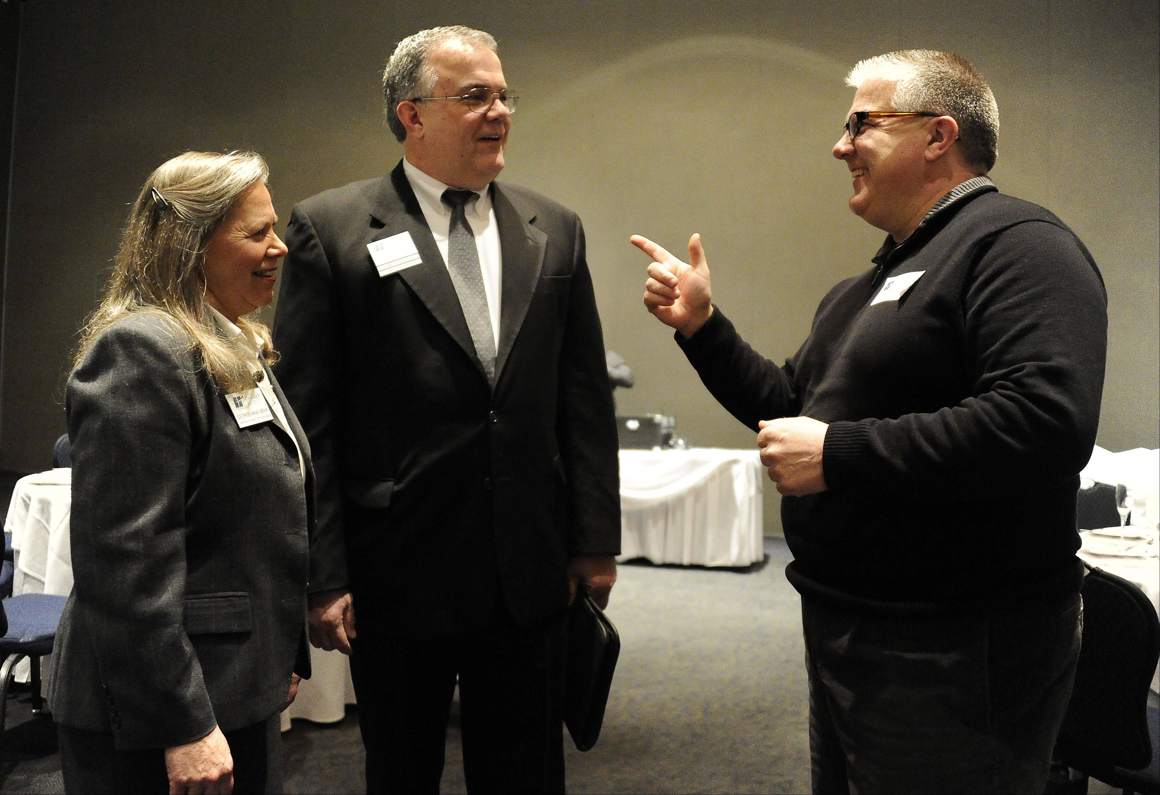 Keith Evans of the Key Financial Insurance Agency of South Barrington, center, talks with the Georgeanna Mehr from Hoffman Estates Community Bank and Jeff Miller from Divine Signs and Graphics at the second annual Celebration of Excellence in Hoffman Estates on Thursday. The bank won the President�s Award later in the night.