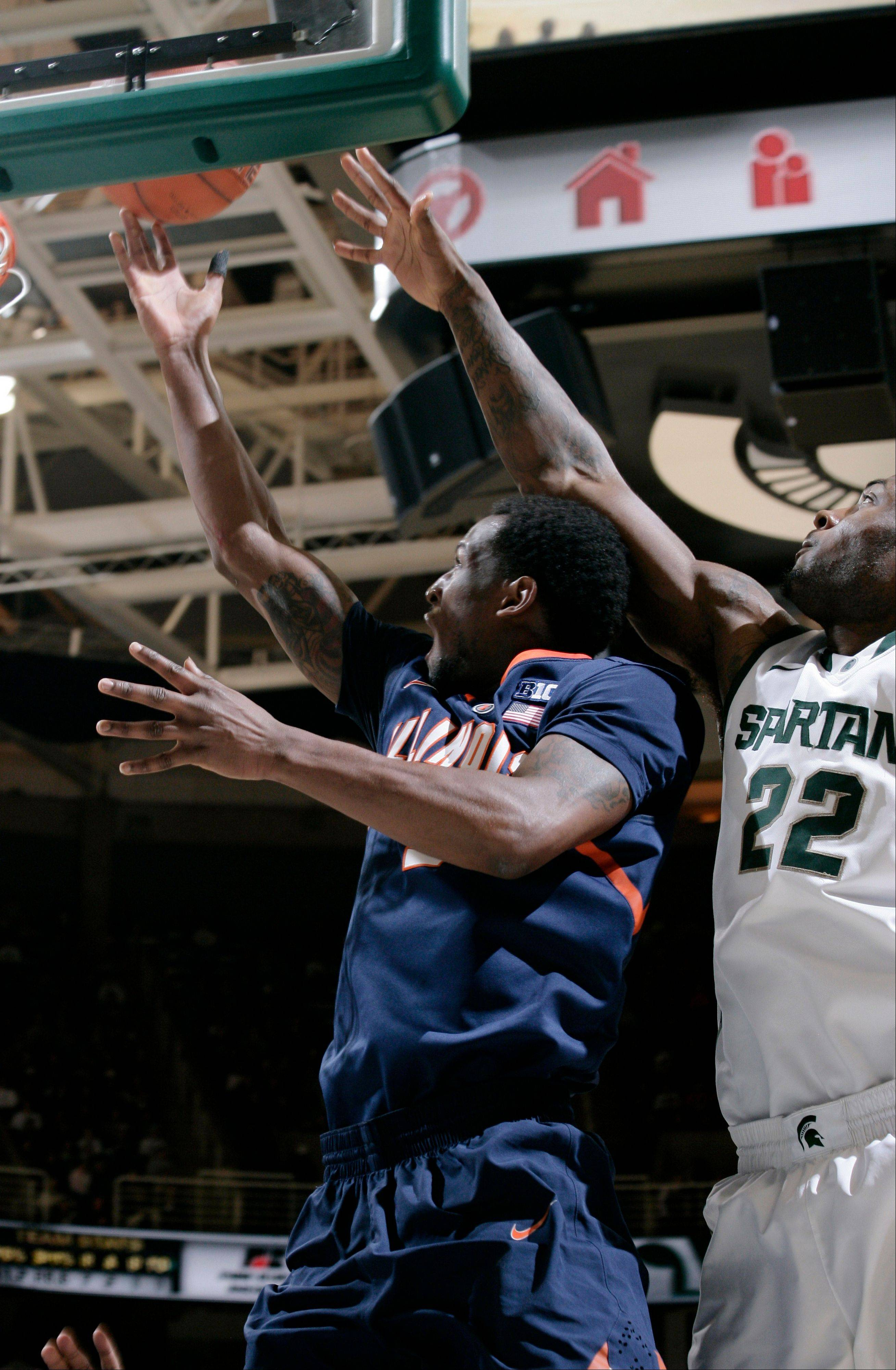 Illinois' D.J. Richardson, left, puts up a layup next to Michigan State's Branden Dawson (22) during the first half of an NCAA college basketball game Thursday in East Lansing, Mich. (AP Photo/Al Goldis)