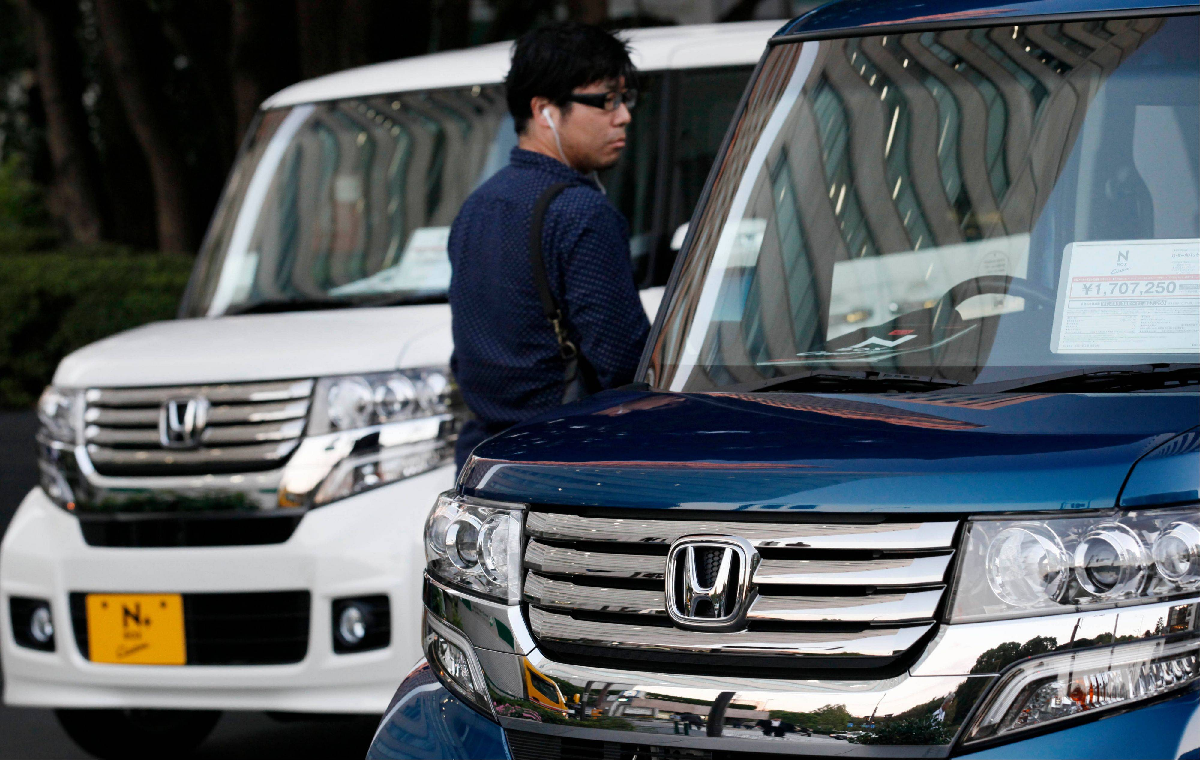 A man inspects Honda vehicles displayed in front of Honda Motor Co. headquarters in Tokyo.