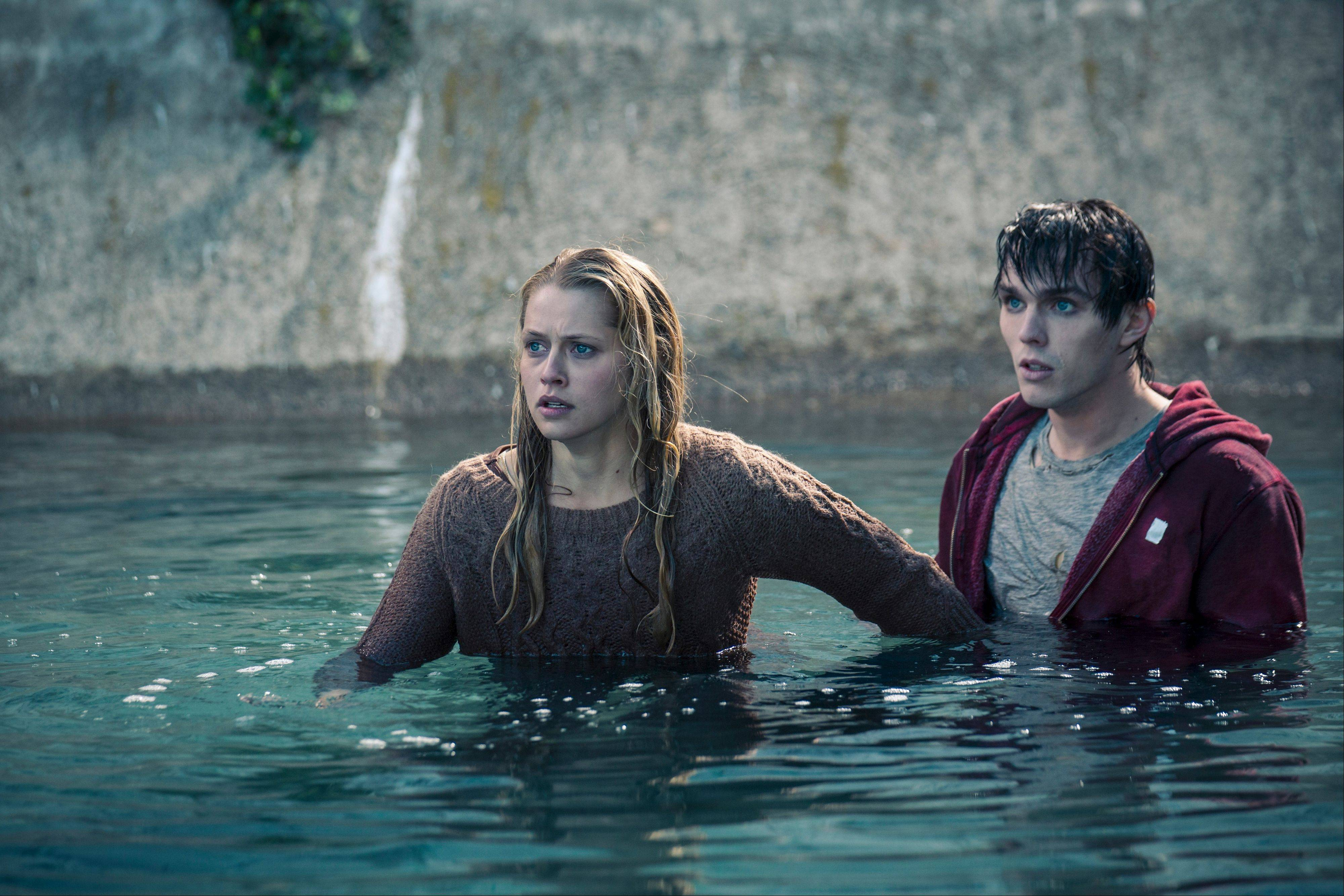 "Julie (Teresa Palmer) protects a zombie named R (Nicholas Hoult) from a bullet to his head in Jonathan Levine's surprisingly sweet undead romance ""Warm Bodies."""