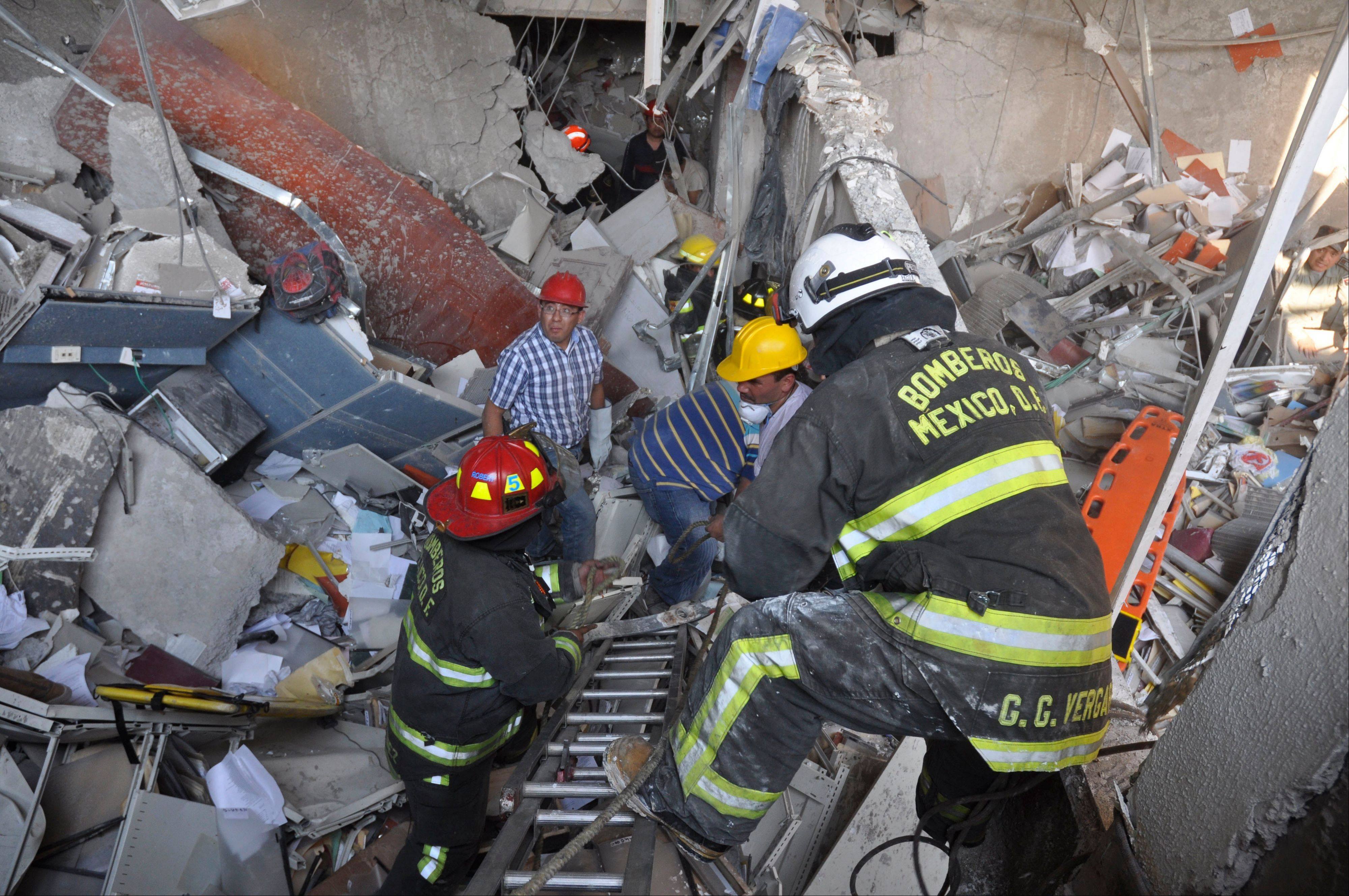 Firefighters and workers dig for survivors after an explosion at an adjacent building to the executive tower of Mexico's state-owned oil company PEMEX in Mexico City on Thursday.