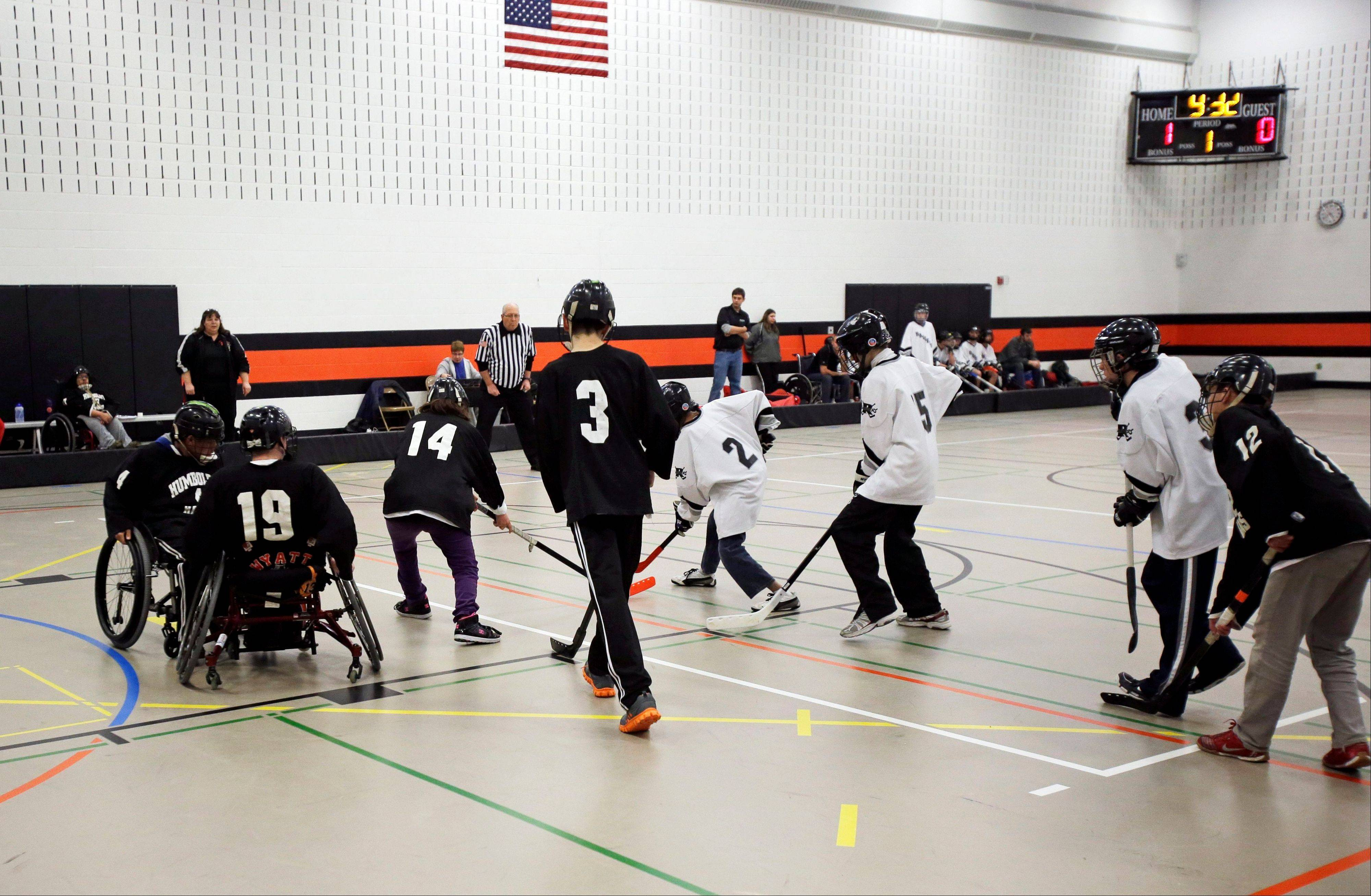"High school students participate in a floor hockey game in St. Paul, Minn., Tuesday. Floor hockey is one of the ""adapted athletics"" programs the state high school league has run since 1992. Minnesota has become a model state as the federal government pushes schools to include more disabled students in sports. Coaching the Hawks is Mary Bohland, background left."