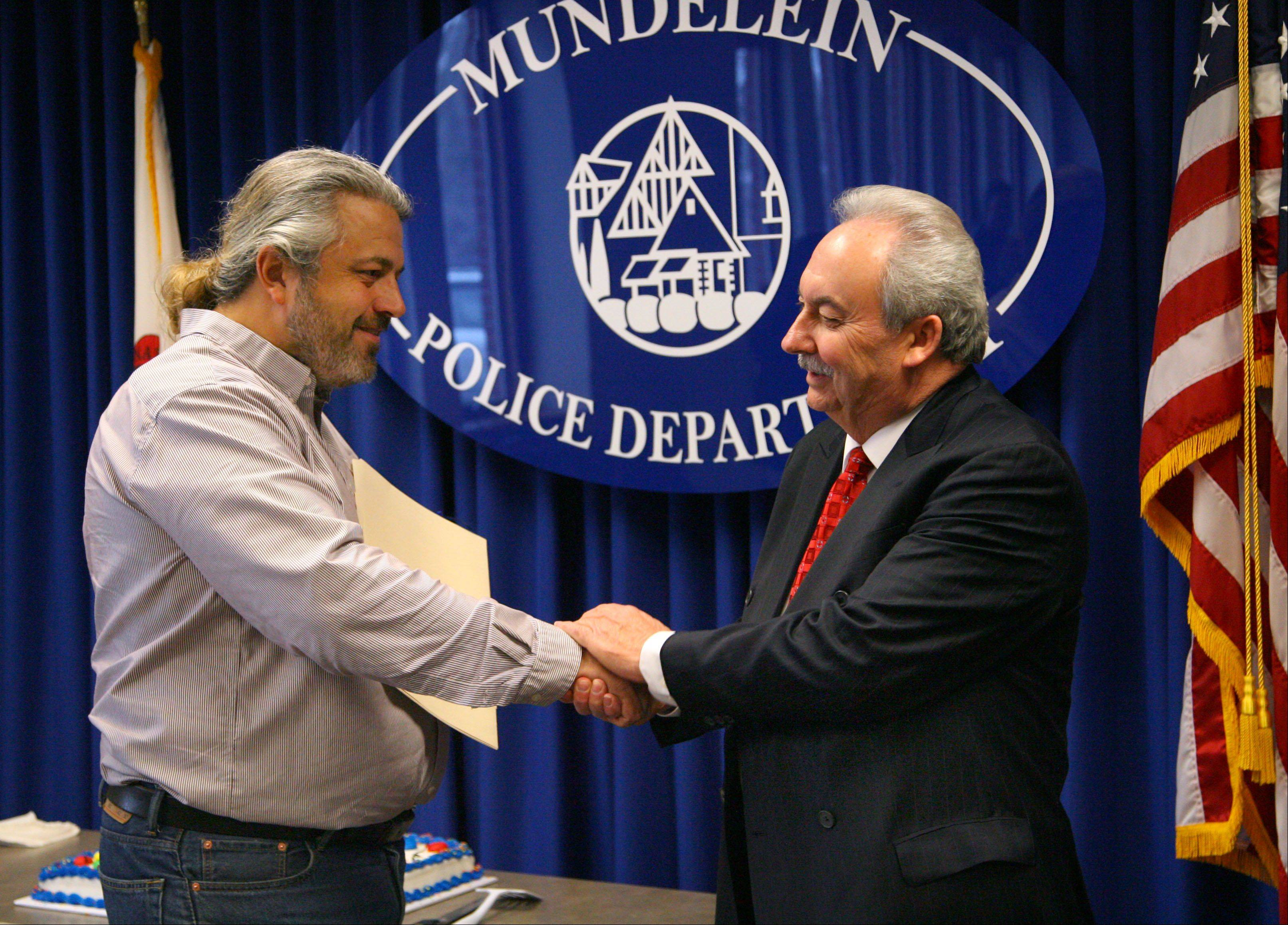 Mundelein Mayor Kenneth H. Kessler, left, shakes hands with outgoing Police Chief Raymond J. Rose on his last official day on the job during a retirement ceremony at the police station Thursday.