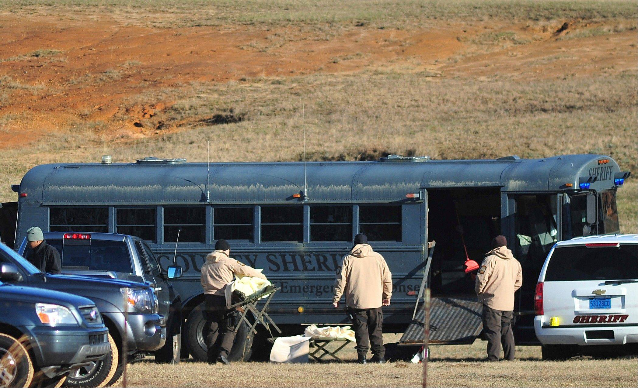 Law enforcement personnel load provisions into a bus during the third day of a hostage crisis involving a 5-year-old boy, in Midland City, Ala, Thursday, Jan 31, 2013. A standoff in rural Alabama went into a second full day Thursday as police surrounded an underground bunker where a retired truck driver was holding a 5-year-old hostage he grabbed off a school bus after shooting the driver dead.