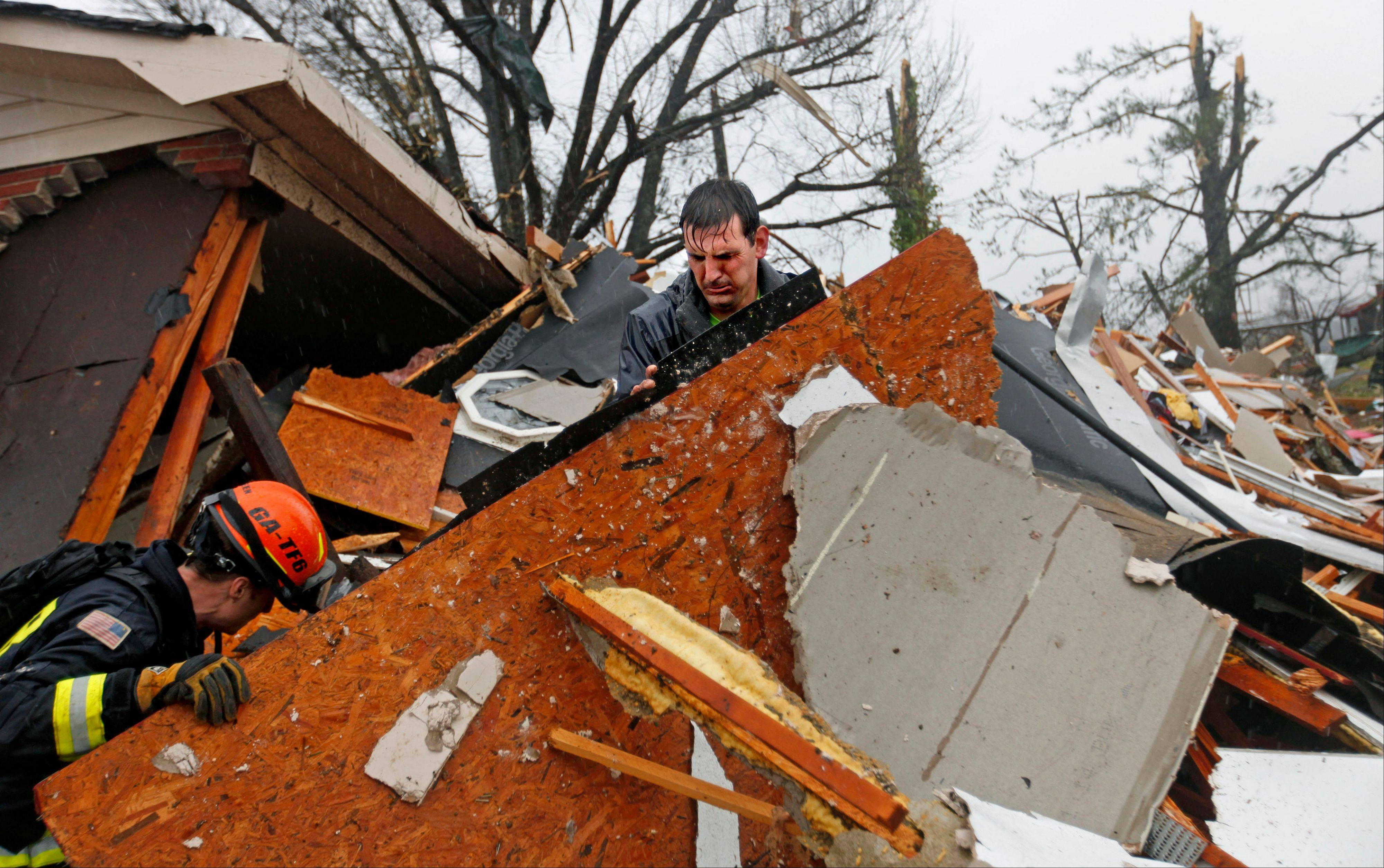 Nathan Varnes, of Cartersville, Ga., right, helps Georgia Search and Rescue firefighter Billy Green, left, search a destroyed home for a dog after a tornado struck, Wednesday, Jan. 30, 2013, in Adairsville, Ga.