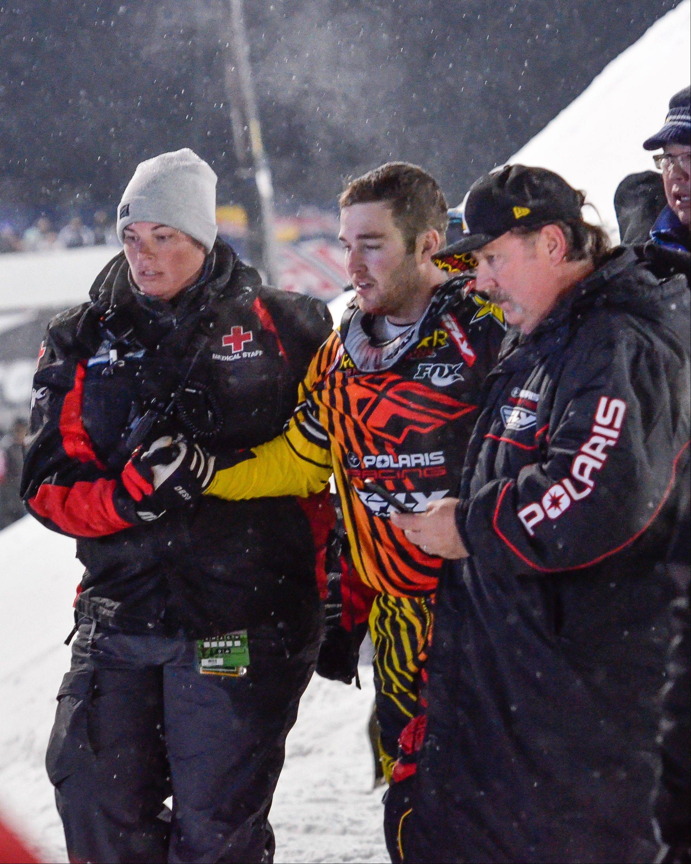 In this photo taken Jan. 24, 2013, Caleb Moore, center, is helped off the snow following his crash during the ESPN Winter X Games snowmobile freestyle competition in Aspen, Colo. Moore died on Thursday, Jan. 31, 2013, after suffering complications from injuries suffered during the crash. He was 25. AP Photo/Aspen Daily News, Chris Council)
