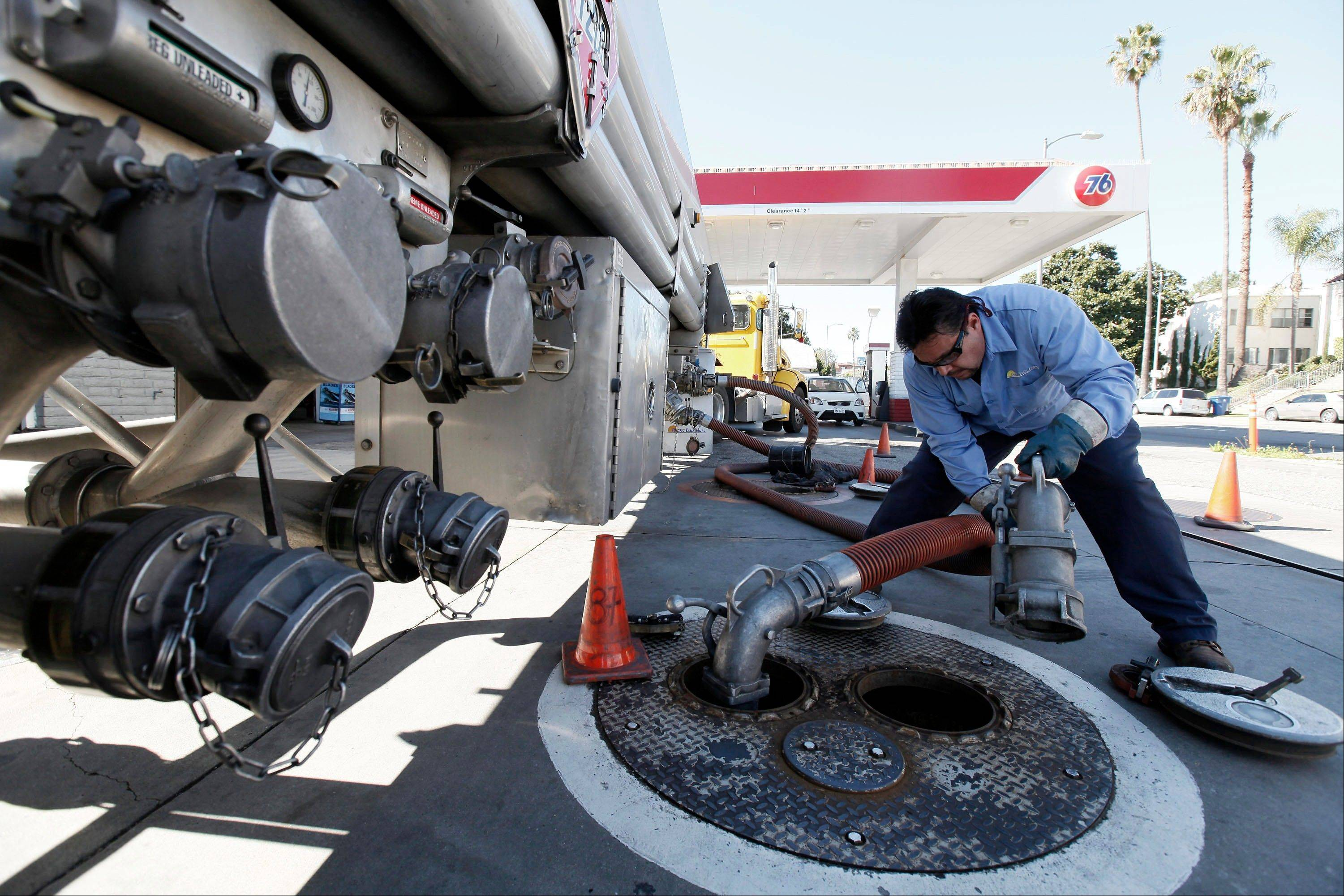 Freddy Lozoga fills an underground tank at a service station Thursday in Los Angeles.
