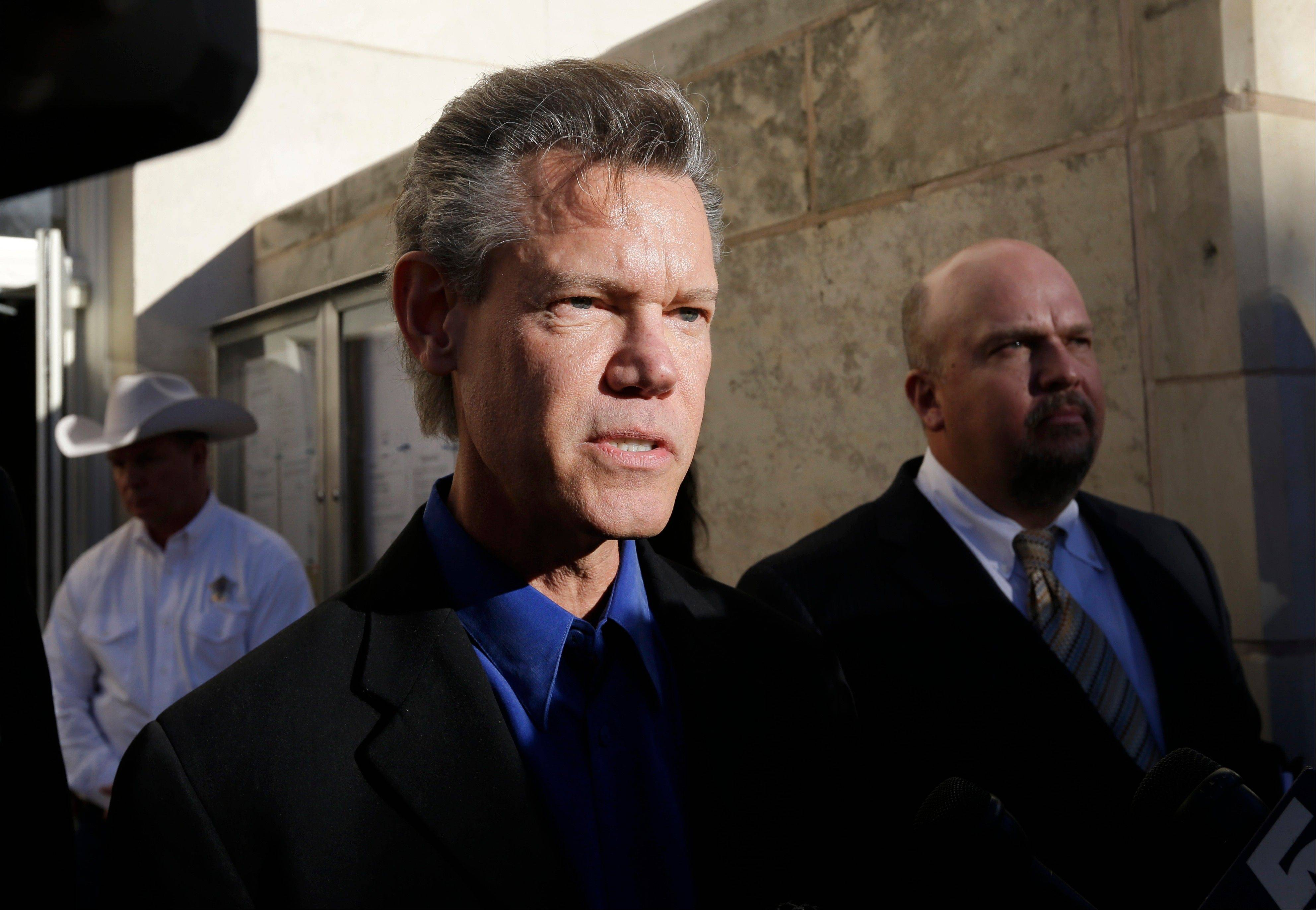 Entertainer Randy Travis, center, makes comments after exiting the Grayson County Courthouse Thursday in Sherman, Texas. Travis plead guilty to driving while intoxicated in a plea agreement with the court and will pay a $2,000 fine and serve a two year probation.