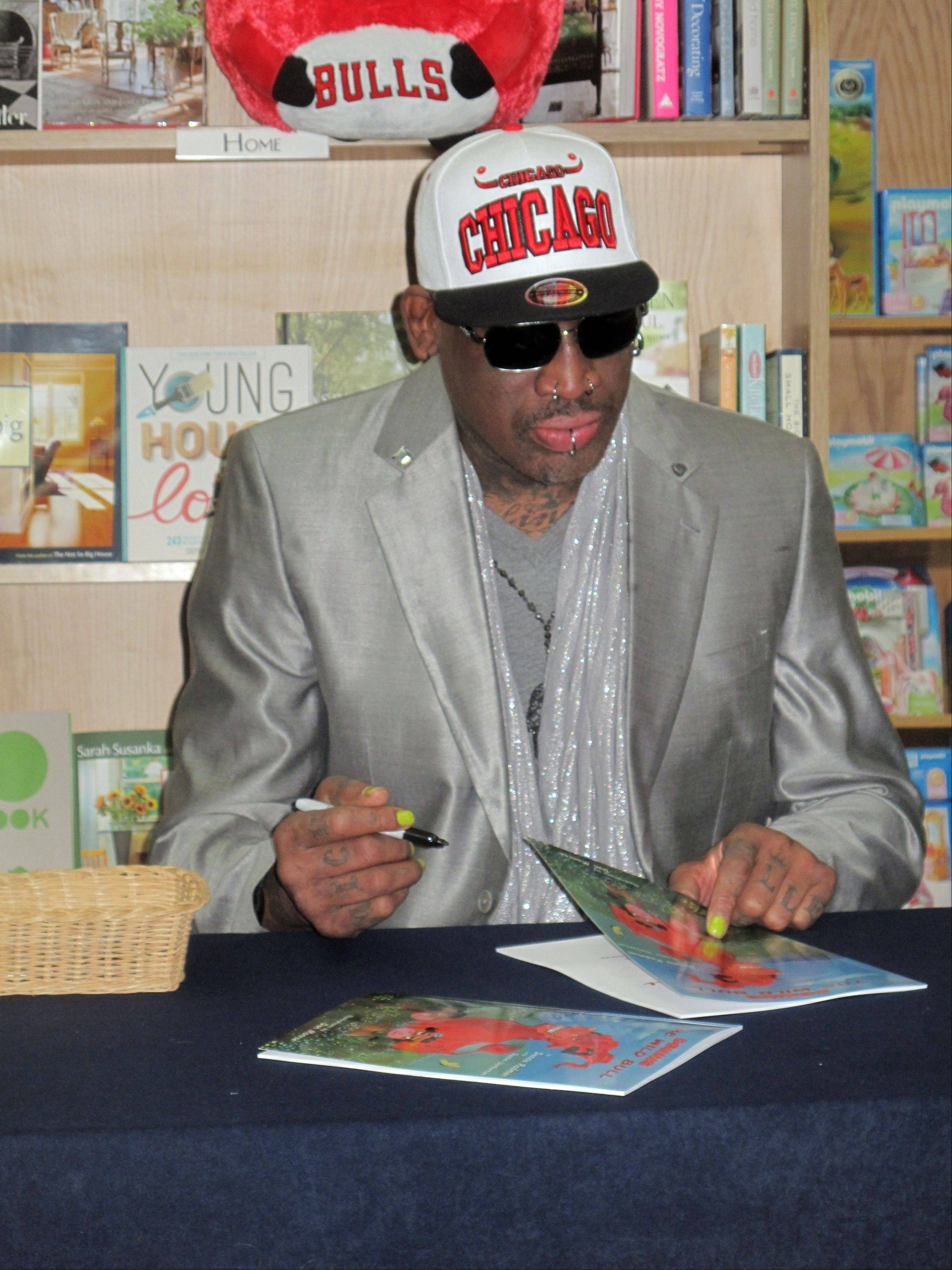"Dennis Rodman signs copies of his children's book ""Dennis The Wild Bull"" on Saturday at Anderson's Bookshop in Naperville."