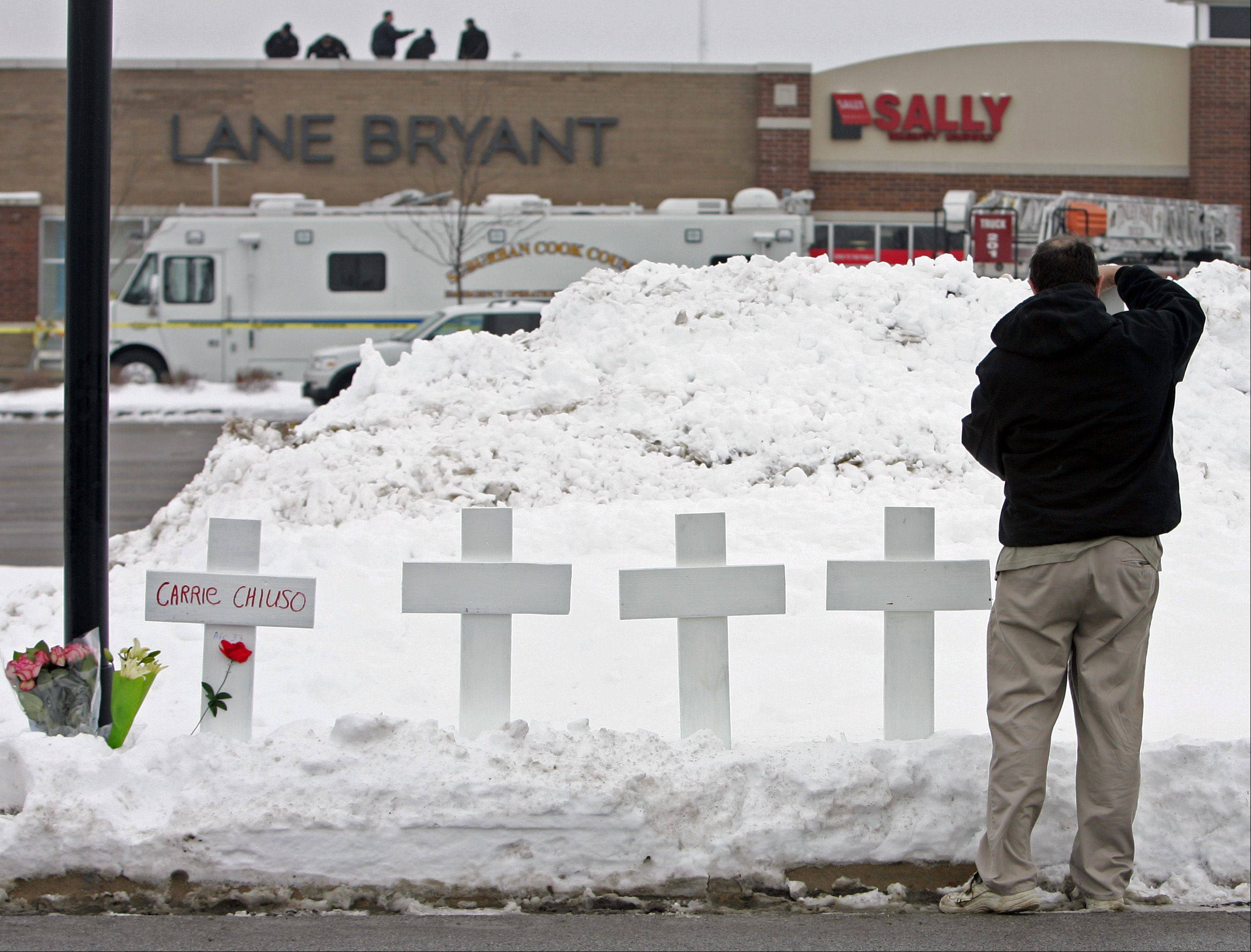 Greg Zanis of Sugar Grove puts up five crosses and leaves flowers at the Lane Bryant store in Tinley Park on Feb. 3, 2008.