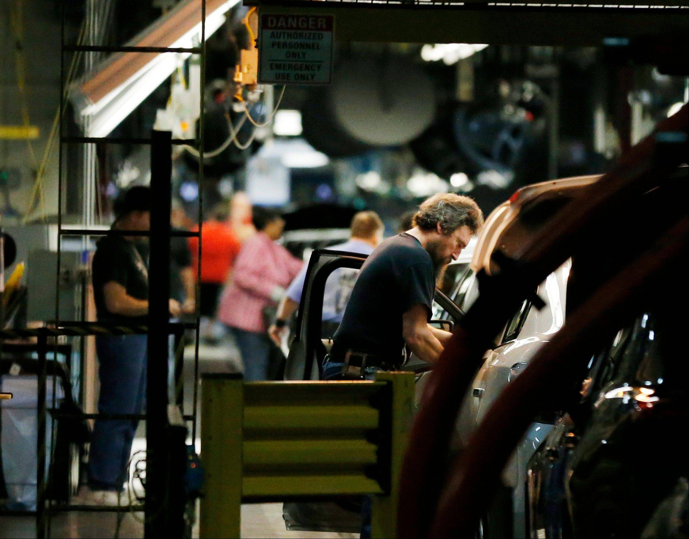 Workers assemble cars along a line at the General Motors Fairfax plant in Kansas City, Kan. U.S. manufacturing activity grew at a faster pace in January, driven by an increase in new orders and more hiring at factories.