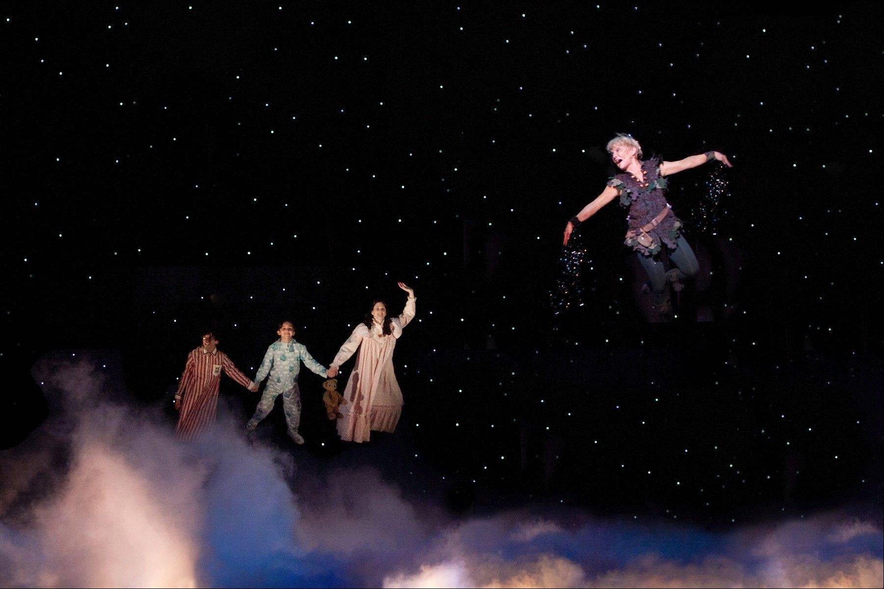 "Peter Pan (Cathy Rigby, right) leads the Darling children John, Michael and Wendy (Lexy Baeza, Hadley Belle Miller and Krista Buccellato) to Neverland in the national tour of ""Peter Pan,"" now playing the Cadillac Palace Theatre in Chicago through Sunday, Feb. 10."