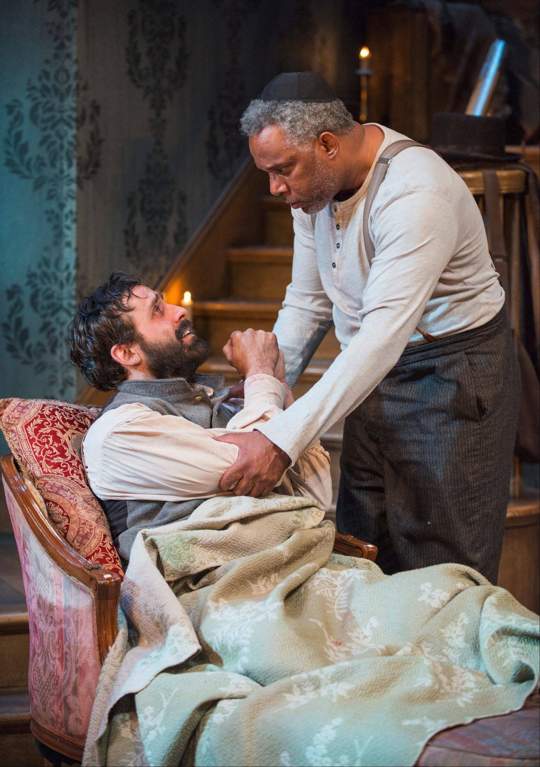 "Guilt-ridden Caleb (Derek Gaspar, left) reveals some gut-wrenching news to Simon (Tim Edward Rhoze), who has managed to retain his moral center in an immoral situation, in Northlight Theatre's Chicago-area premiere of ""The Whipping Man"" by Matthew Lopez."