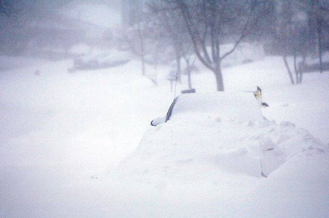 A car is 3/4 buried on a residential street in Elgin Wednesday morning as the area endures one of the worst blizzards in memory.