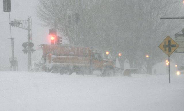 A snowplow on Arlington Heights Road crosses Northwest Highway Wednesday morning in Arlington Heights. The National Weather Service is saying travel by car may cost your life.