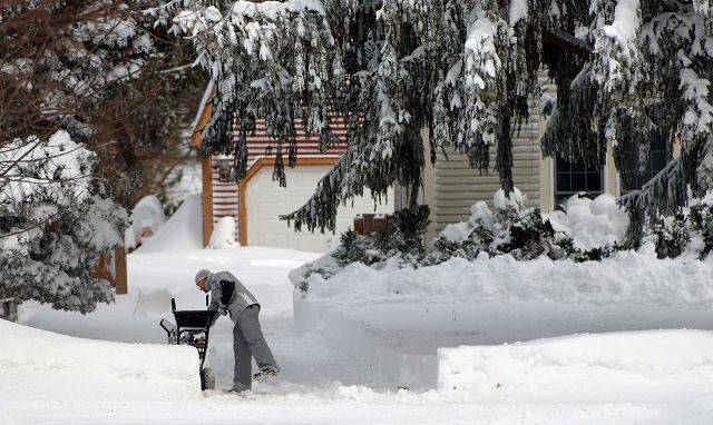 A Crystal Lake resident hacks away at his driveway with a snowblower along Route 176 Wednesday morning.