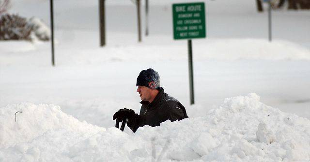Crystal Lake resident David Ferguson takes a break from digging out his driveway Wednesday morning.