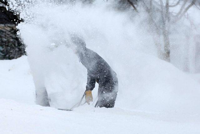Dan Hess of Elgin gets a face full of snow as he tries to clear his driveway Wednesday morning.