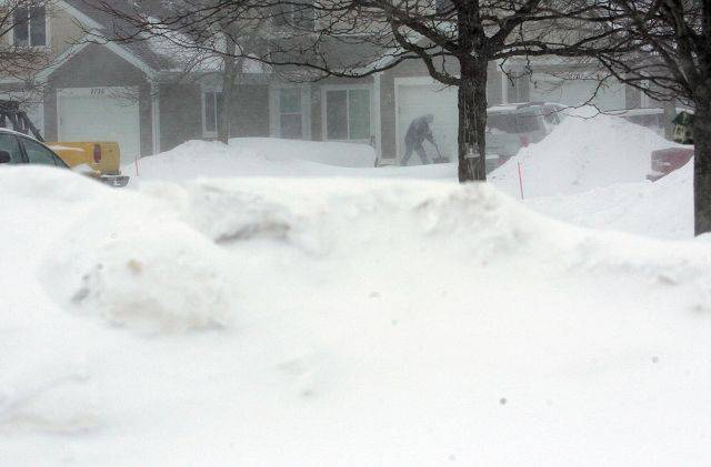 People try to dig themselves out from the blizzard in Aurora on Wednesday.