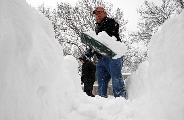 William and his son Jacob RaRocca dig out their driveway in Palatine Wendesday.