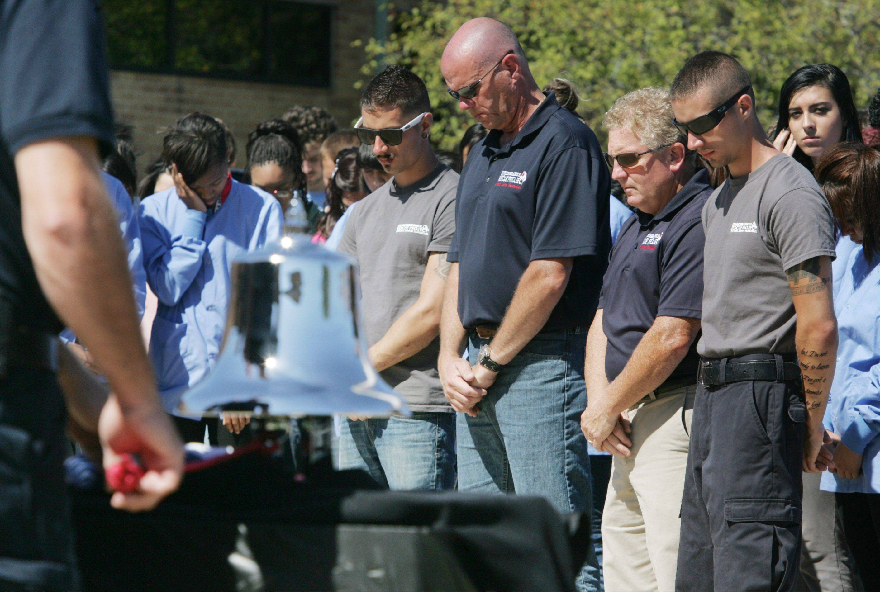 Remembrance Rescue Project members Corey Vaughn, left, Scott Vaughn, John Jacquette, and Brian Vaughn bow their heads as the fire bell is rung during a 9/11 ceremony at the Lake County High Schools Technology Campus in Grayslake. The group brought New York Fire Department Rescue 5 engine to show the students.    The fire truck was on the scene in New York on Sept. 11, 2001, when the two World Trade Center towers collapsed.