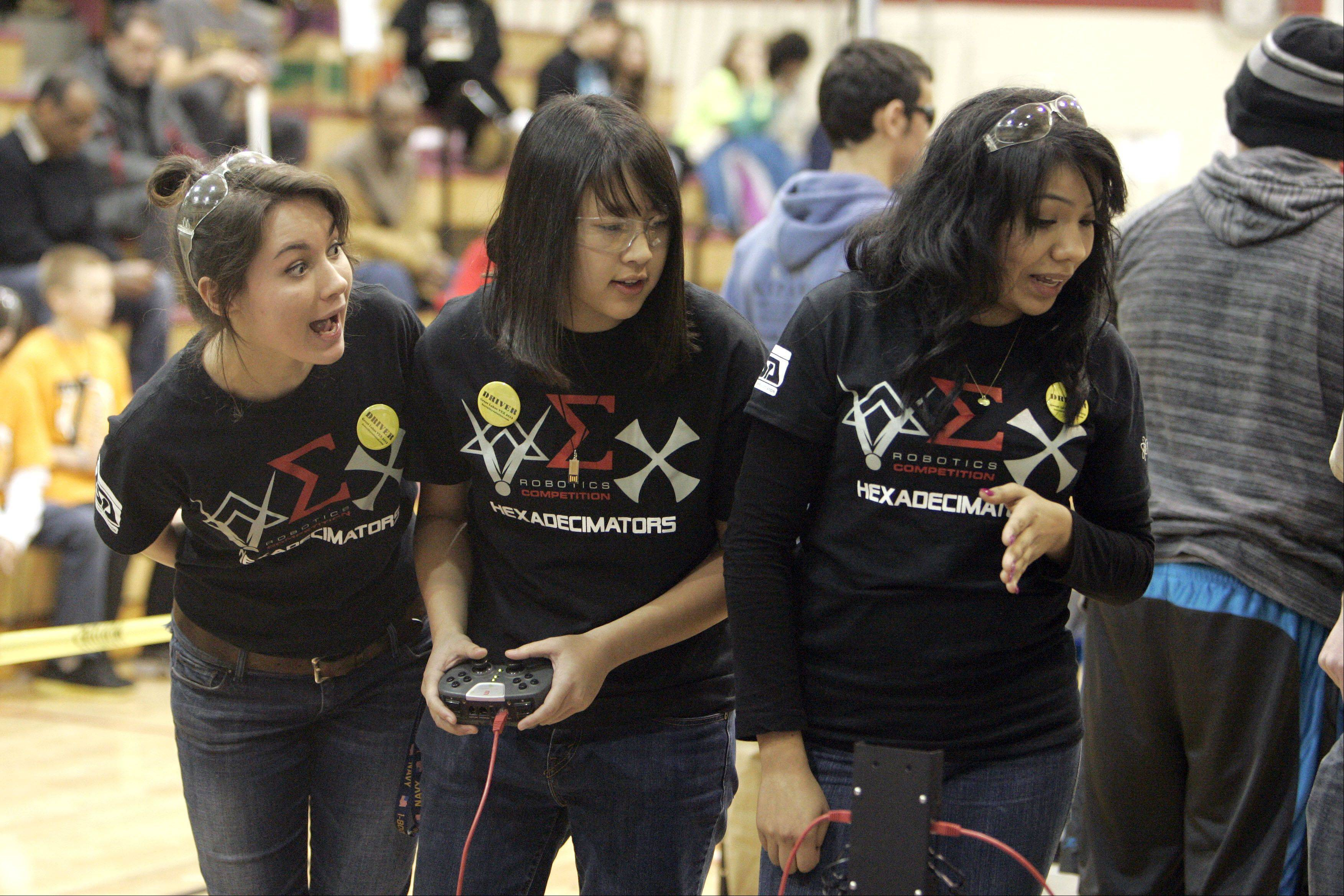 Brian Hill/bhill@dailyherald.comSophomore Madeline Koldos, from left, Thida Vonguilay, and Lissette Beltran, both seniors, of the Hex Adecimators of Bartlett High School discuss the intricate movements of their robot during the competition. The competition included 48 teams from the Midwest.