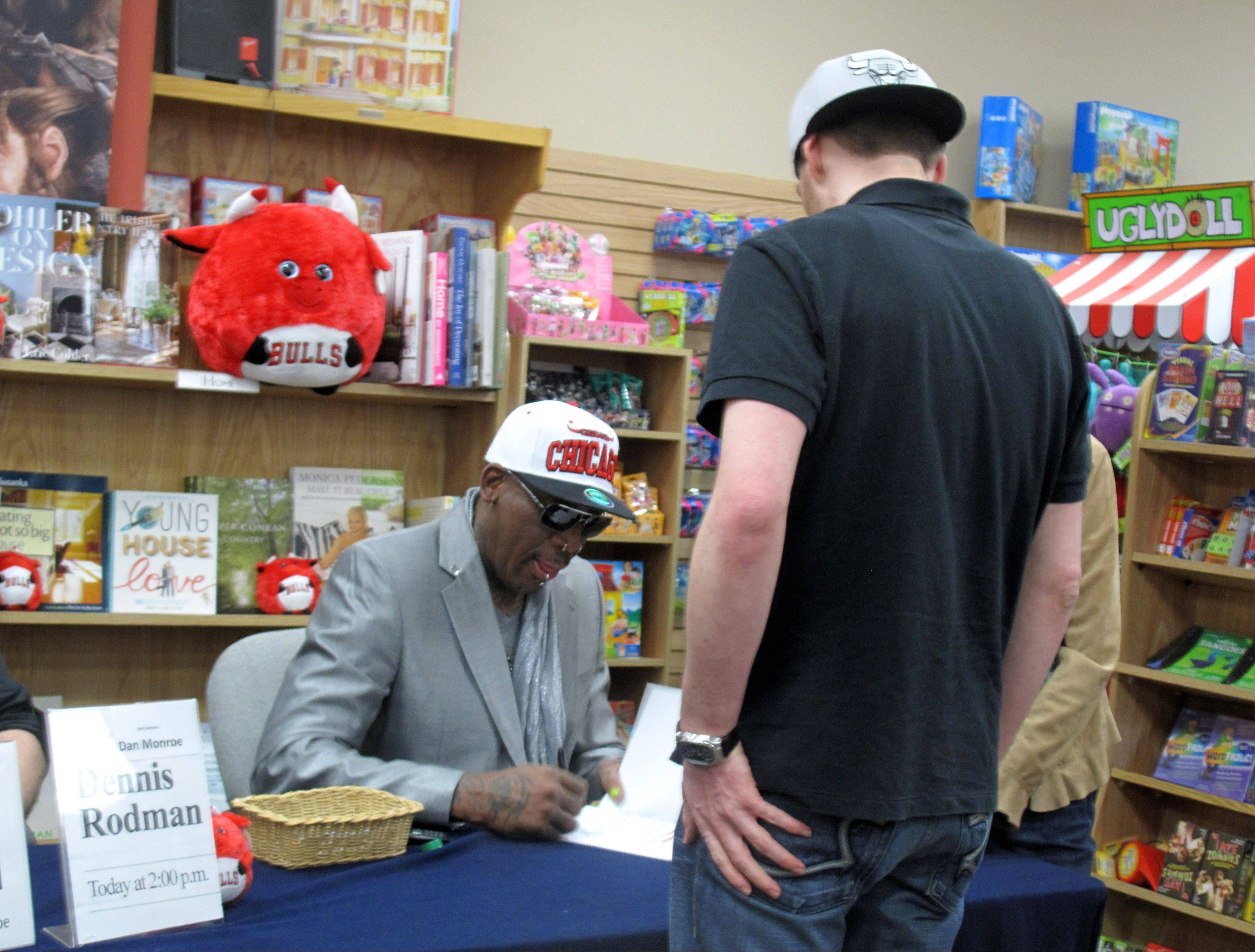 "Former Bulls forward Dennis Rodman signs a copy of his newly released children's book, ""Dennis The Wild Bull,"" for Matthew Dunn of Oswego on Saturday at Anderson's Bookshop in Naperville."