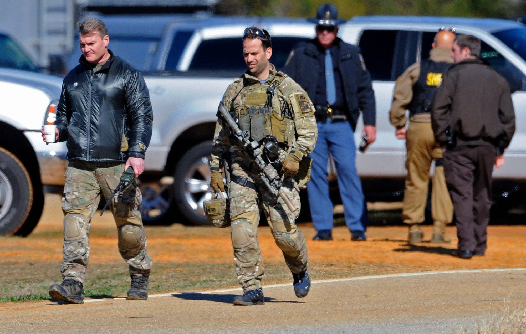 Law officers at the Dale County hostage scene in Midland City, Ala. on Thursday morning, Jan. 31, 2013. A gunman holed up in a bunker with a 6-year-old hostage has kept law officers at bay since the standoff began when he killed a school bus driver and dragged the boy away, authorities said.