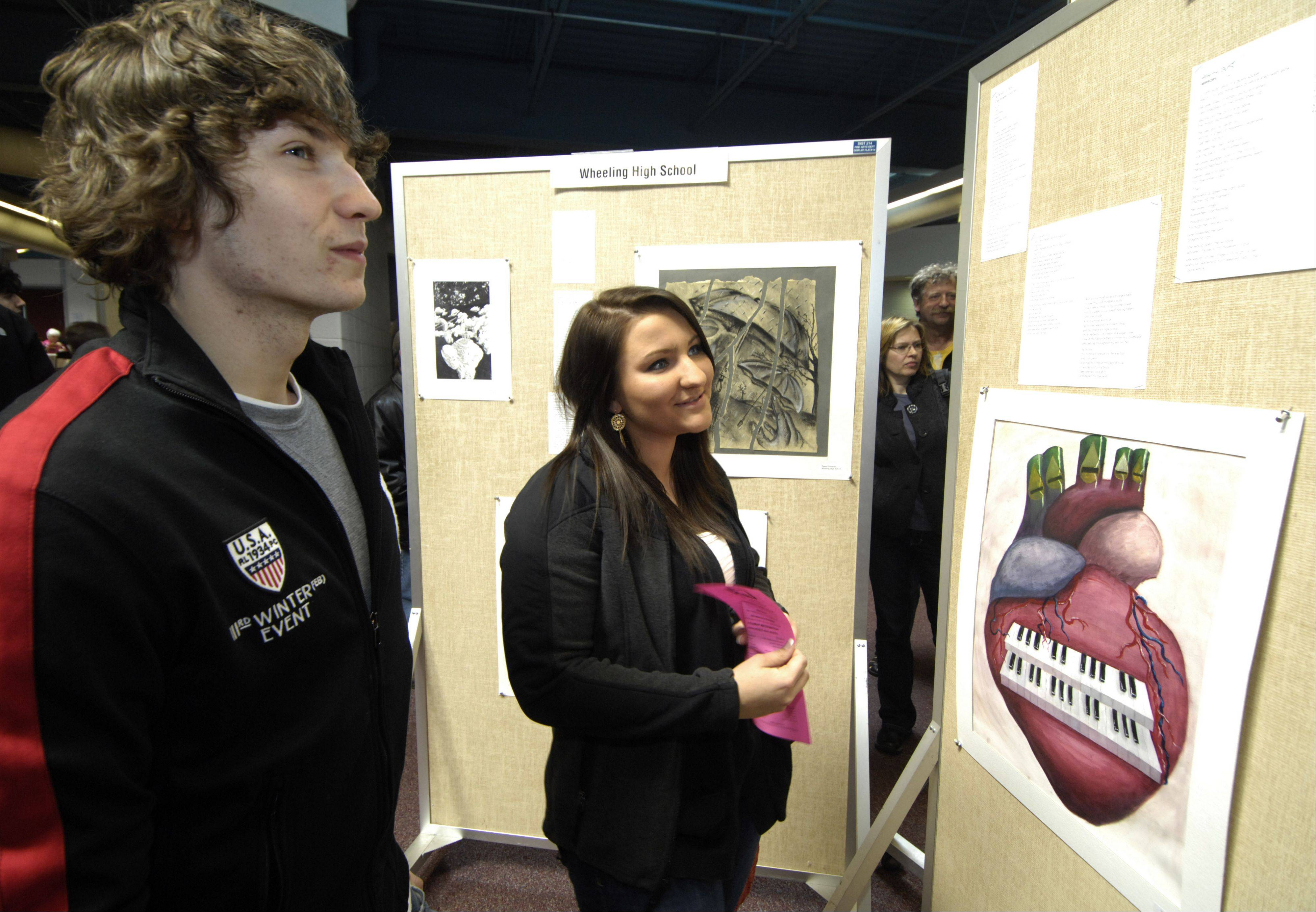 Amanda Faust of Rolling Meadows High School views her winning poem with Jakub Grab-Lucki at the 2012 Arts Unlimited reception at Forest View Educational Center.