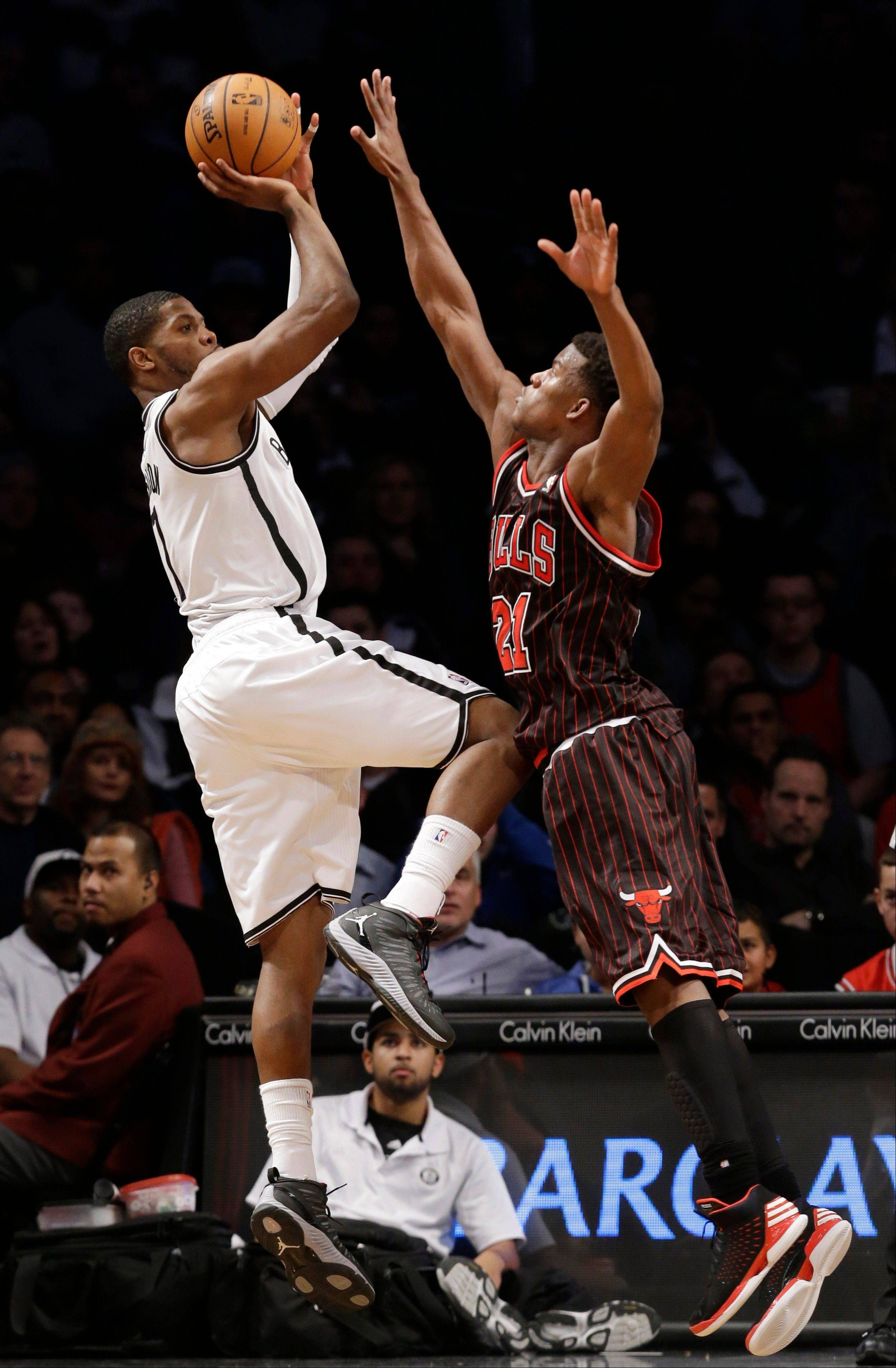 Brooklyn Nets guard C.J. Watson (1) shoots a three-point basket as Chicago Bulls forward Jimmy Butler (21) defends in the second half of their NBA basketball game at the Barclays Center, Friday, Feb. 1, 2013, in New York. Watson had 13 points as the Nets defeated the Bulls 93-89.