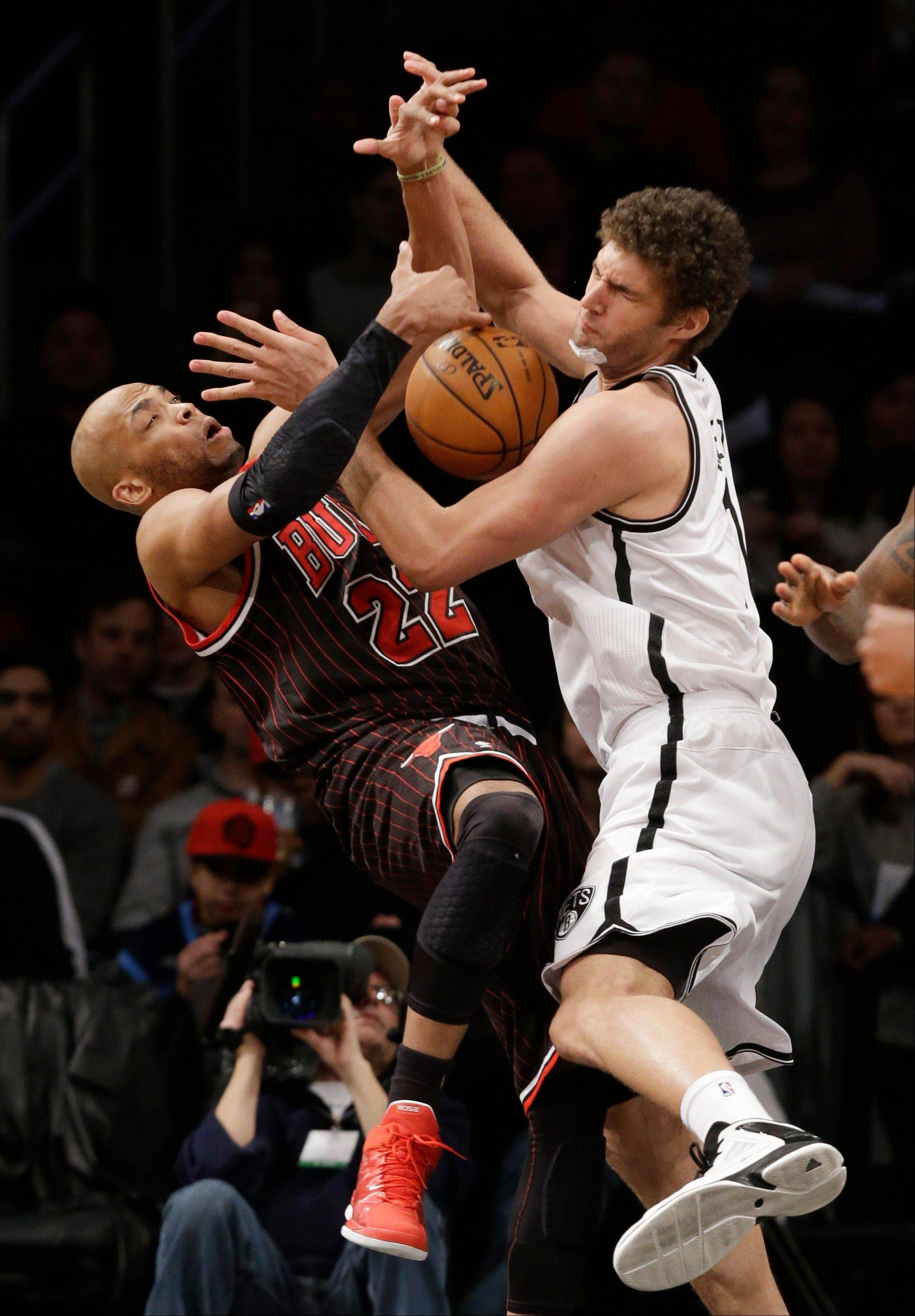 Brooklyn Nets center Brook Lopez, right, becomes entangled with Chicago Bulls forward Taj Gibson (22) in the second half of their NBA basketball game at the Barclays Center, Friday, Feb. 1, 2013, in New York. Lopez had 20 points as the Nets defeated the Bulls 93-89.