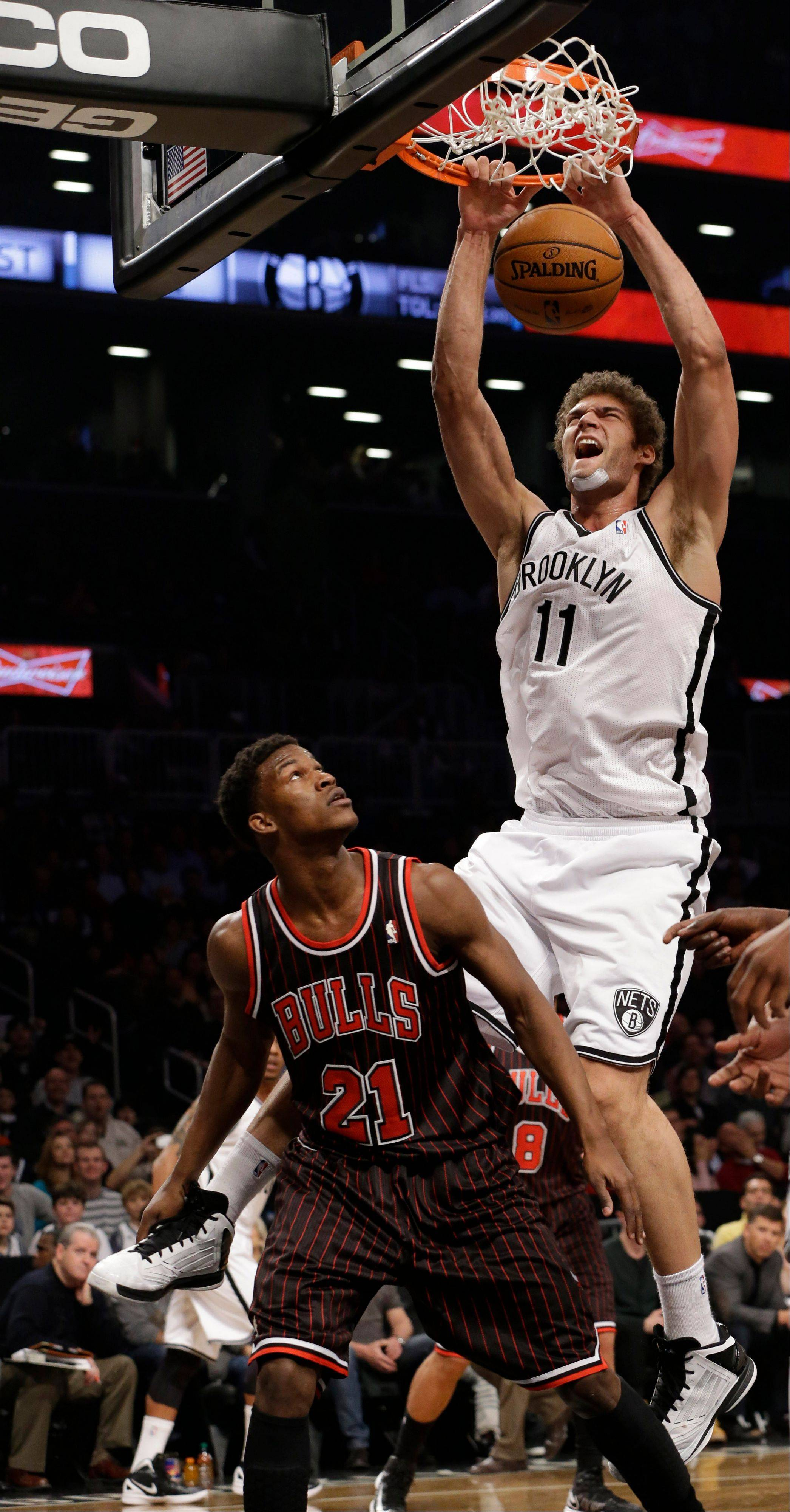Brooklyn Nets center Brook Lopez, top, dunks over Chicago Bulls forward Jimmy Butler (21) in the first half of an NBA basketball game at the Barclays Center, Friday, Feb. 1, 2013,in New York.