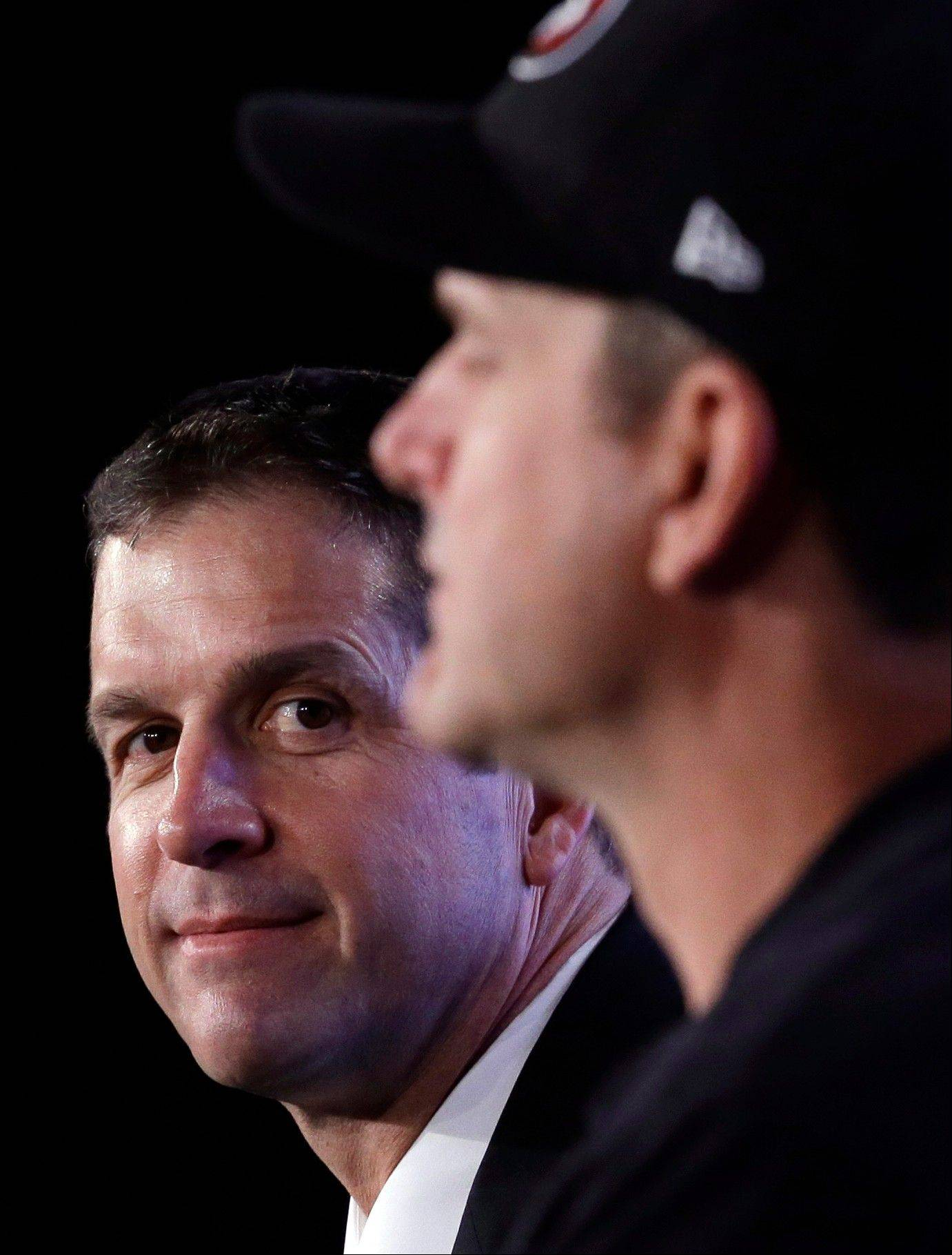 "Ravens head coach John Harbaugh, left, listens to brother Jim during a joint news conference Friday in New Orleans. The duo had a good time, at one point remarking that Jim probably couldn't spell ""philosophical"" or ""commonalities."""