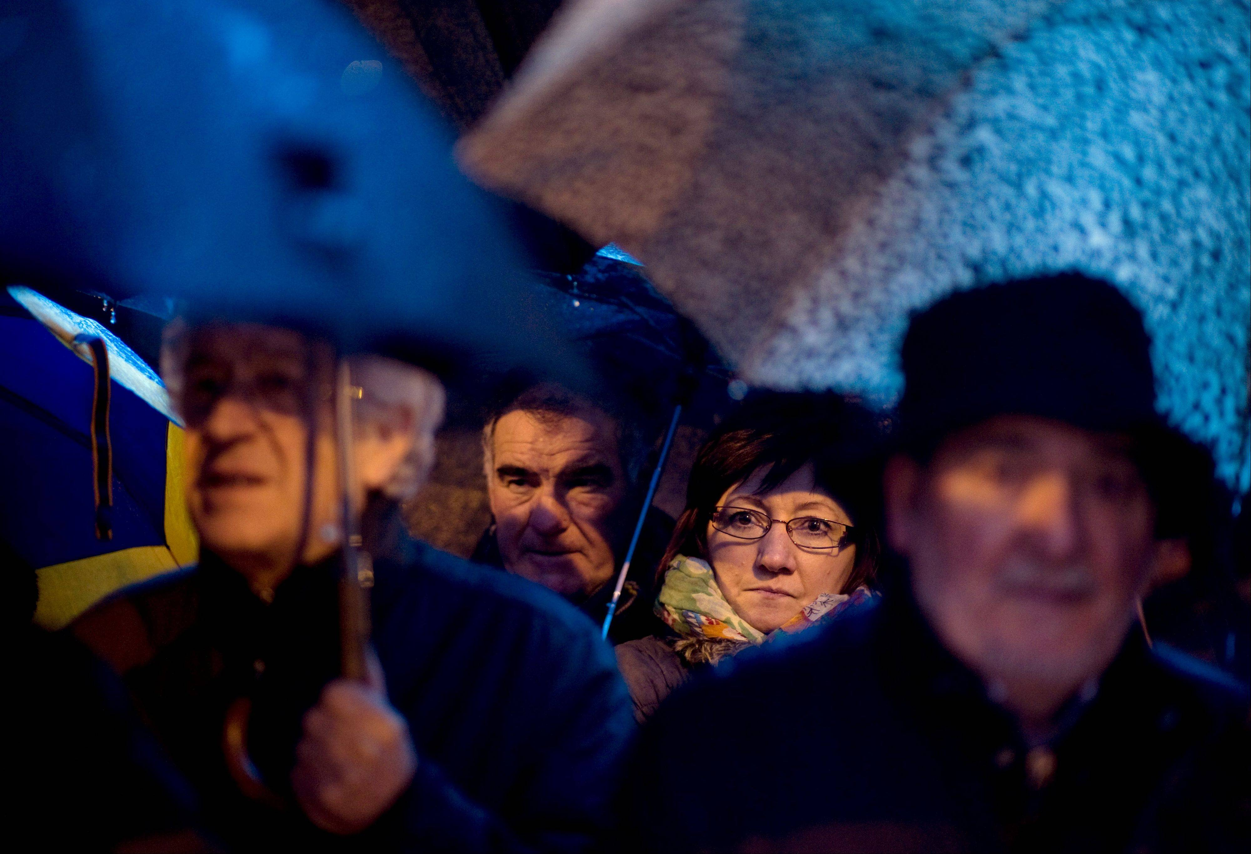 People shelter from the rain under umbrellas Saturday as they march against corruption of Spanish politicians, in Pamplona northern Spain.
