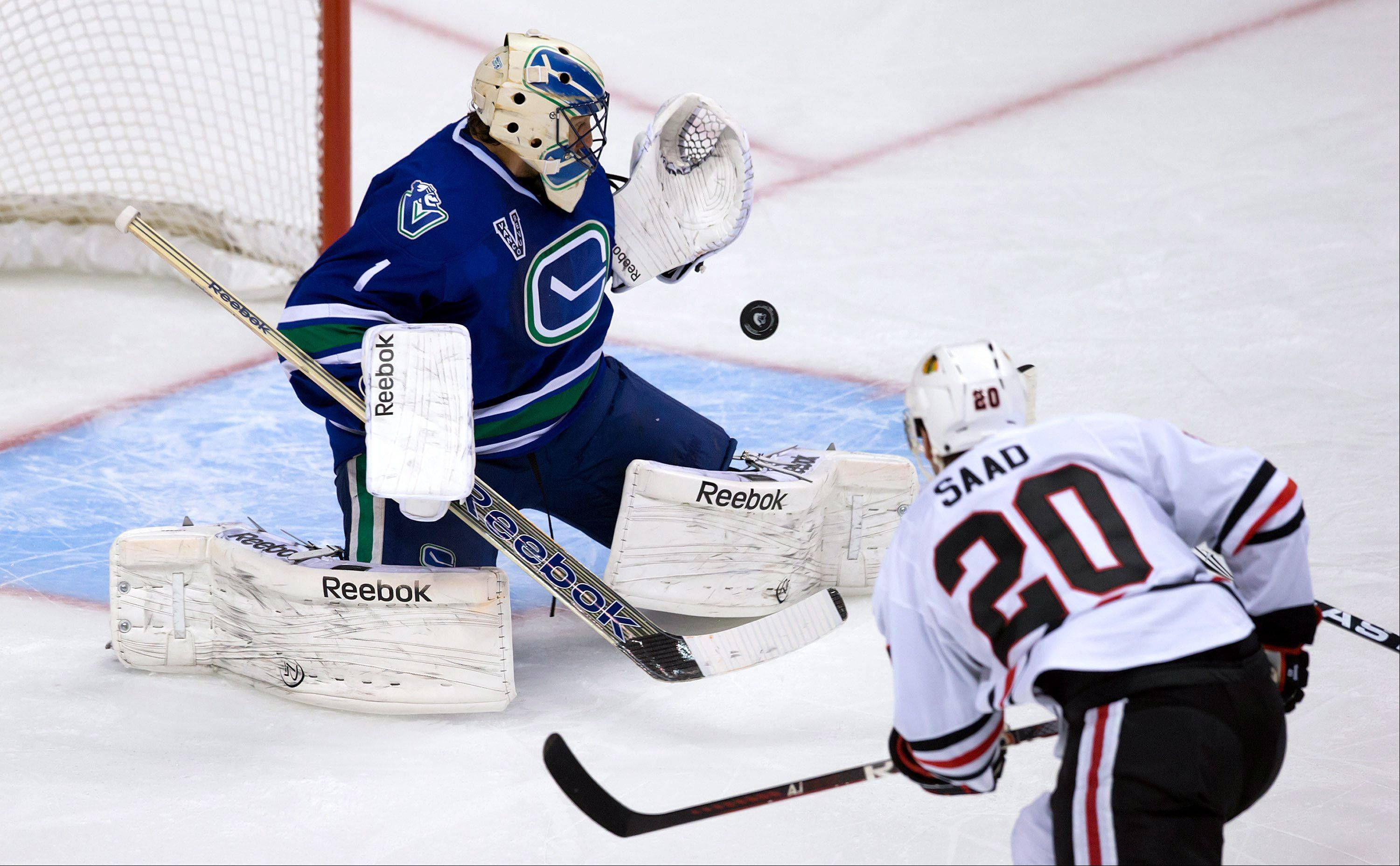 Vancouver Canucks' goalie Roberto Luongo, left, stops Chicago Blackhawks' Brandon Saad during the second period of an NHL hockey game in Vancouver, British Columbia, on Friday, Feb. 1, 2013.