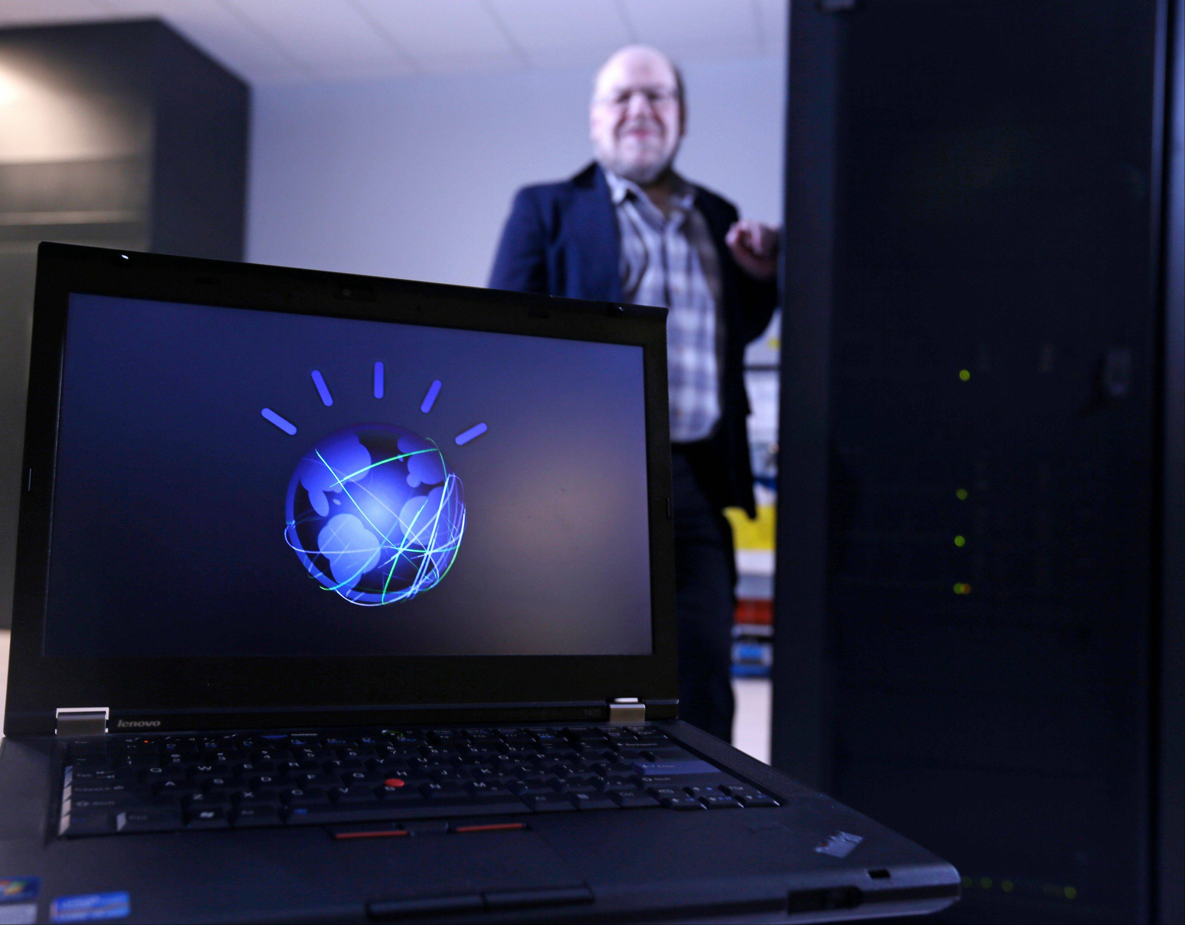 "Jim Hendler, who heads the computer science department at Rensselaer Polytechnic Institute, poses next to the supercomputer Watson at the Computational Center for Nanotechnology Innovations in Troy, N.Y. Watson, the question-answering supercomputer best known for beating human champions on ""Jeopardy!,"" is going to college. IBM is announcing Wednesday that it will provide a Watson system to RPI, the first time a version of the computer is being sent to a university. The avatar on the computer screen represented Watson on ""Jeopardy!."""