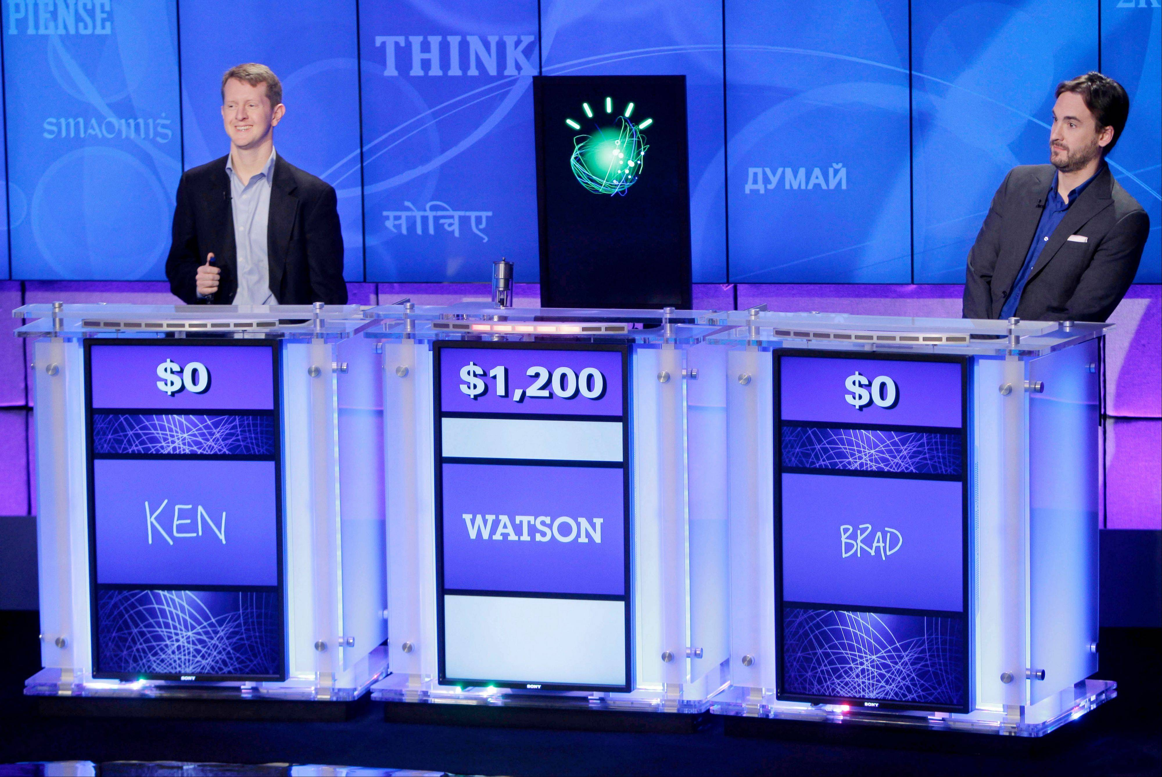 """Jeopardy!"" champions Ken Jennings, left, and Brad Rutter, right, flank a prop representing Watson during a practice round of the ""Jeopardy!"" quiz show in Yorktown Heights, N.Y."