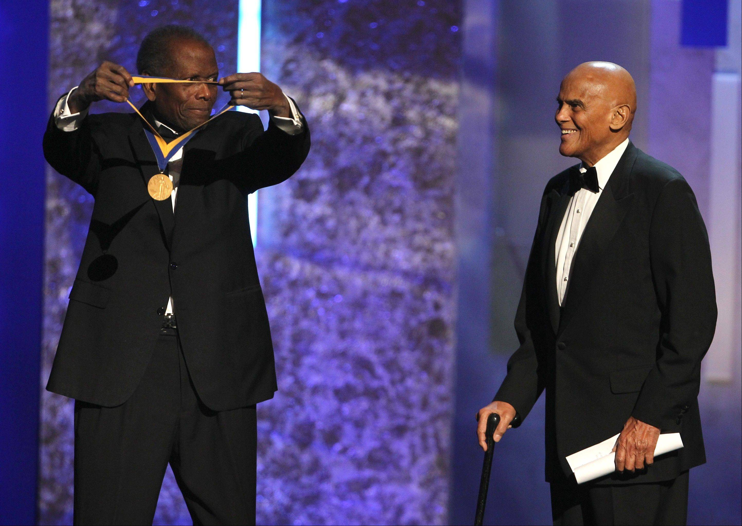 Sidney Poitier, left, presents the Spingarn award to Harry Belafonte at the 44th Annual NAACP Image Awards at the Shrine Auditorium in Los Angeles on Friday, Feb. 1, 2013.