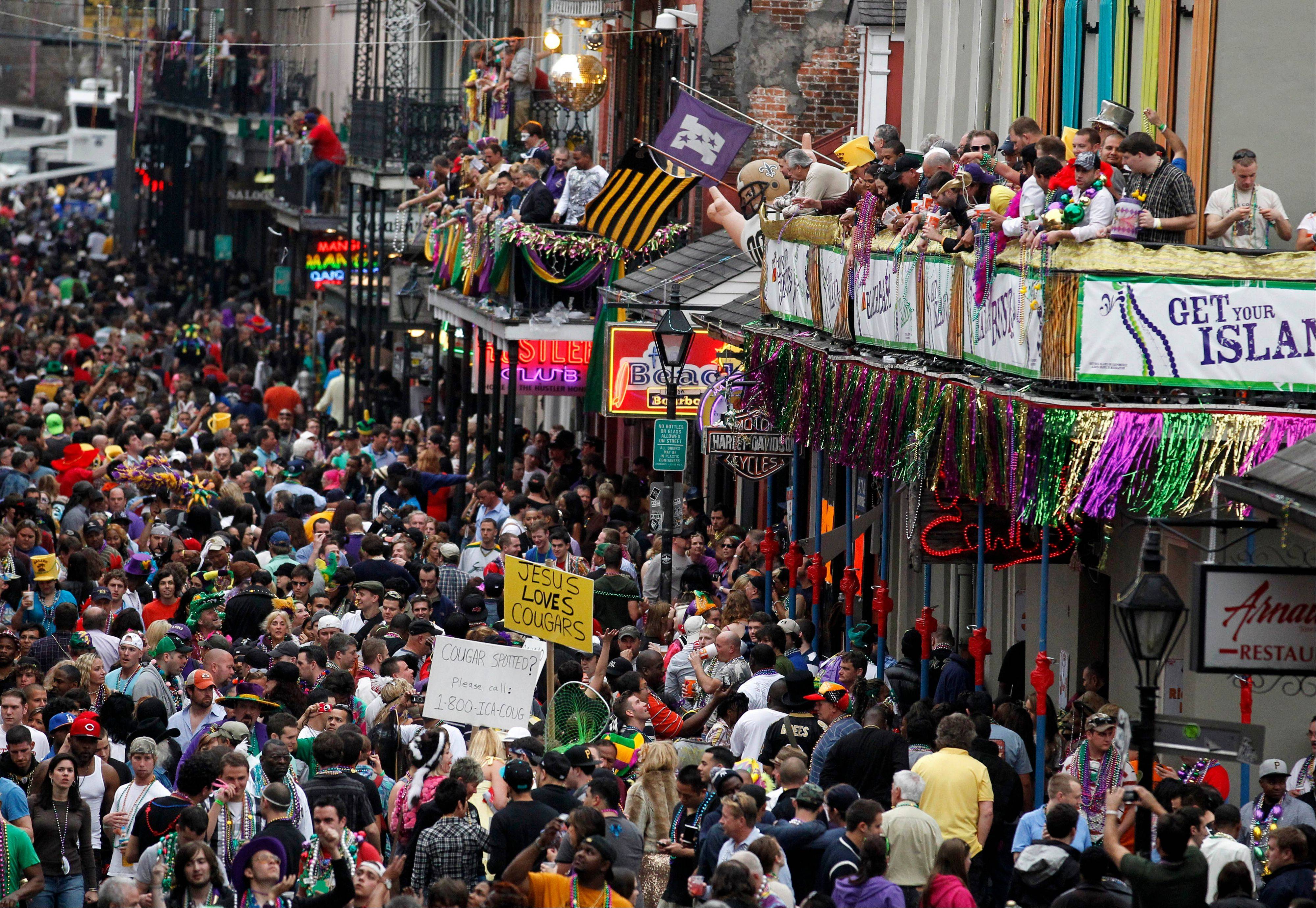 Crowds congregate on Bourbon Street for festivities outside the Royal Sonesta Hotel in the French Quarter on Mardi Gras, one of the biggest free parties in the world.