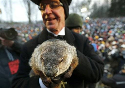 Groundhog Club co-handler Ron Ploucha holds the weather predicting groundhog, Punxsutawney Phil, after the club said Phil did not see his shadow and there will be an early spring, on Groundhog Day, today, Feb. 2, 2013, in Punxsutawney, Pa.