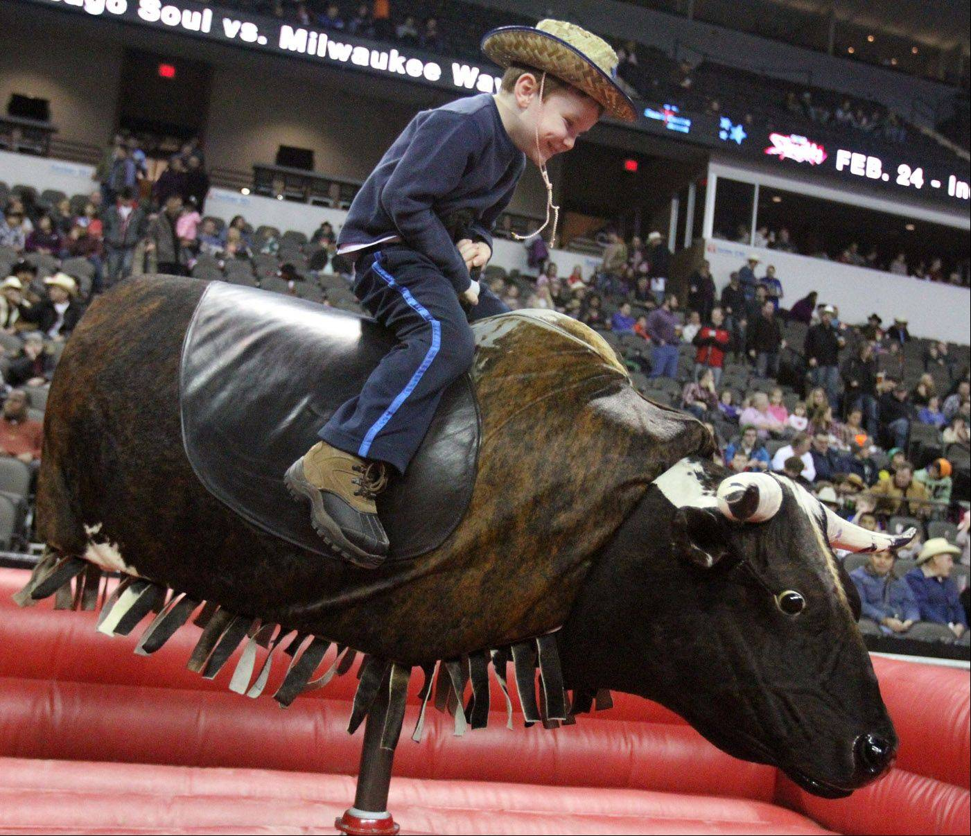 Ryan Giczkowski, 6, of Streamwood, rides the mechanical bull before the Professional Championship Bullrider's World Tour Finale V at the Sears Centre in Hoffman Estates on Saturday, February 2, 2013.