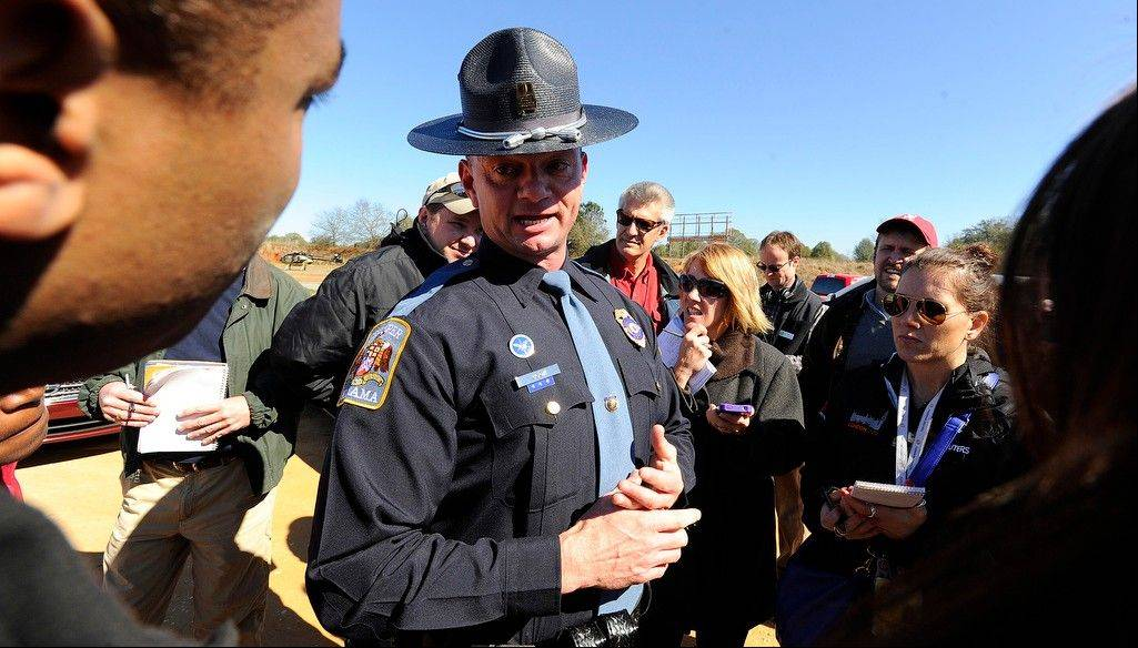 Alabama state trooper Kevin Cook, center, speaks to media Saturday, in Midland City, Ala.